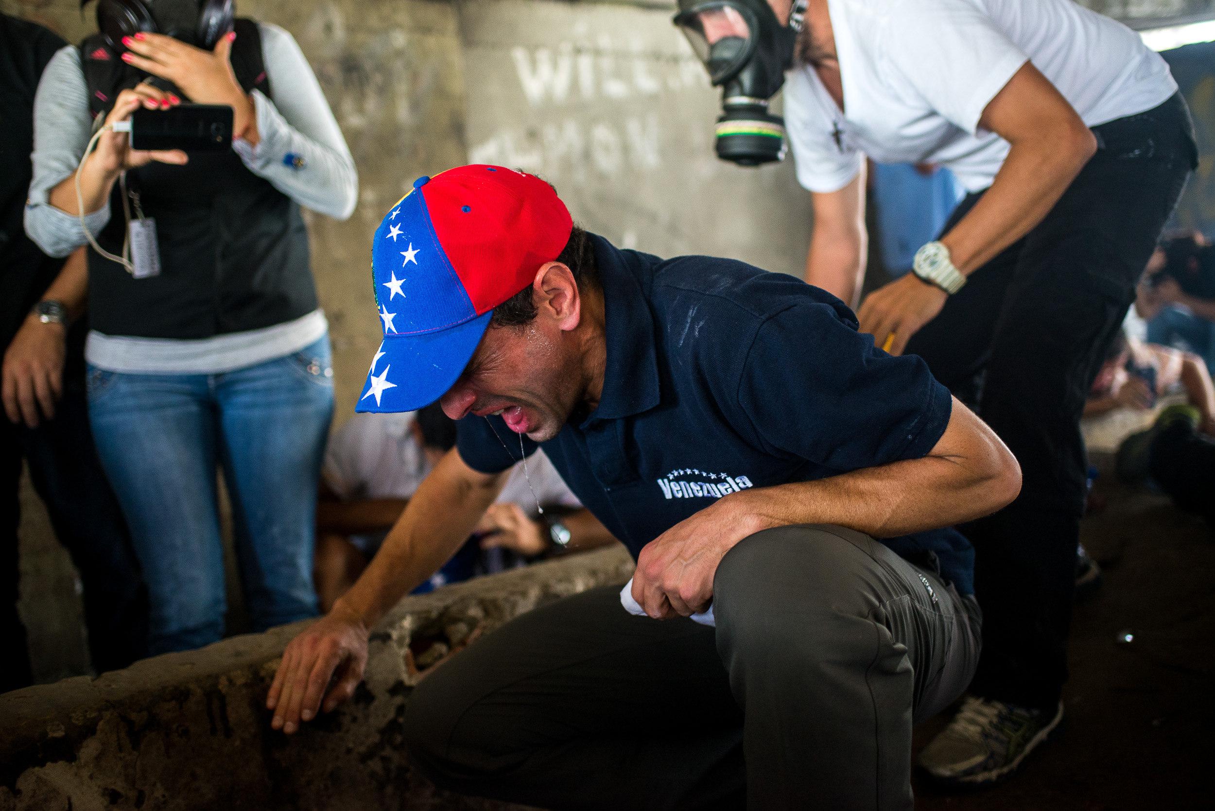 CAR005. CARACAS (VENEZUELA), 19/04/2017.- El líder opositor Henrique Capriles reacciona a los gases lacrimógenos durante una manifestación opositora que intentaba llegar a la Defensoría del Pueblo hoy, miércoles 19 de abril de 2017, en Caracas (Venezuela.). La policía disolvió hoy con gases lacrimógenos una de las marchas opositoras en el centro de Caracas que pretendía llegar a la sede de la Defensoría del Pueblo, mientras que desde otra de las concentraciones antichavistas en esa zona de la ciudad se reportó una persona muerta. Venezuela es escenario el día de hoy de marchas a favor y en contra del Gobierno a las que cada uno de los bandos ha convocado para medir fuerzas en la calle. EFE/Manaure Quintero