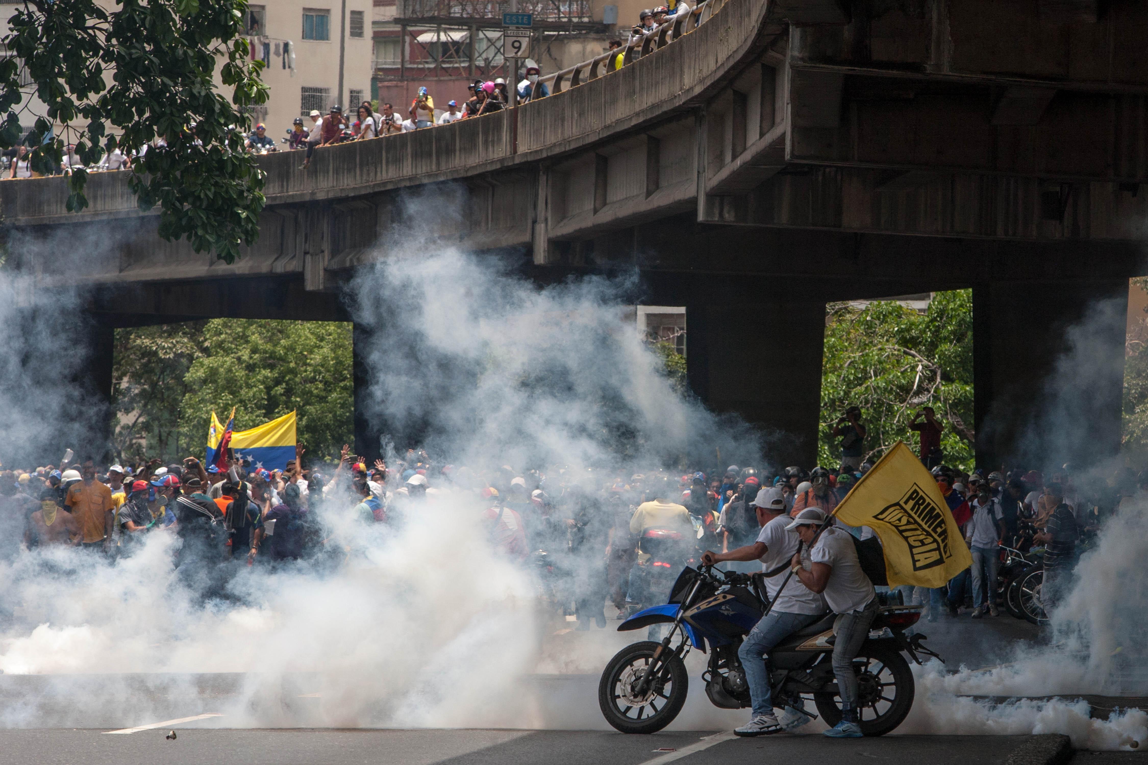 CAR211. CARACAS (VENEZUELA), 19/04/2017 - Un grupo de manifestantes se enfrenta con la policía durante una protesta en contra del Gobierno venezolano hoy, miércoles 19 de abril de 2017, en Caracas (Venezuela). Centenares de opositores en distintos puntos de caracas se enfrentaron hoy a los cuerpos de seguridad para mantenerse en las calles protestando, pese al uso de bombas lacrimógenas por parte de las fuerzas policiales para dispersar y bloquear el paso de las marchas. EFE/CRISTIAN HERNANDEZ