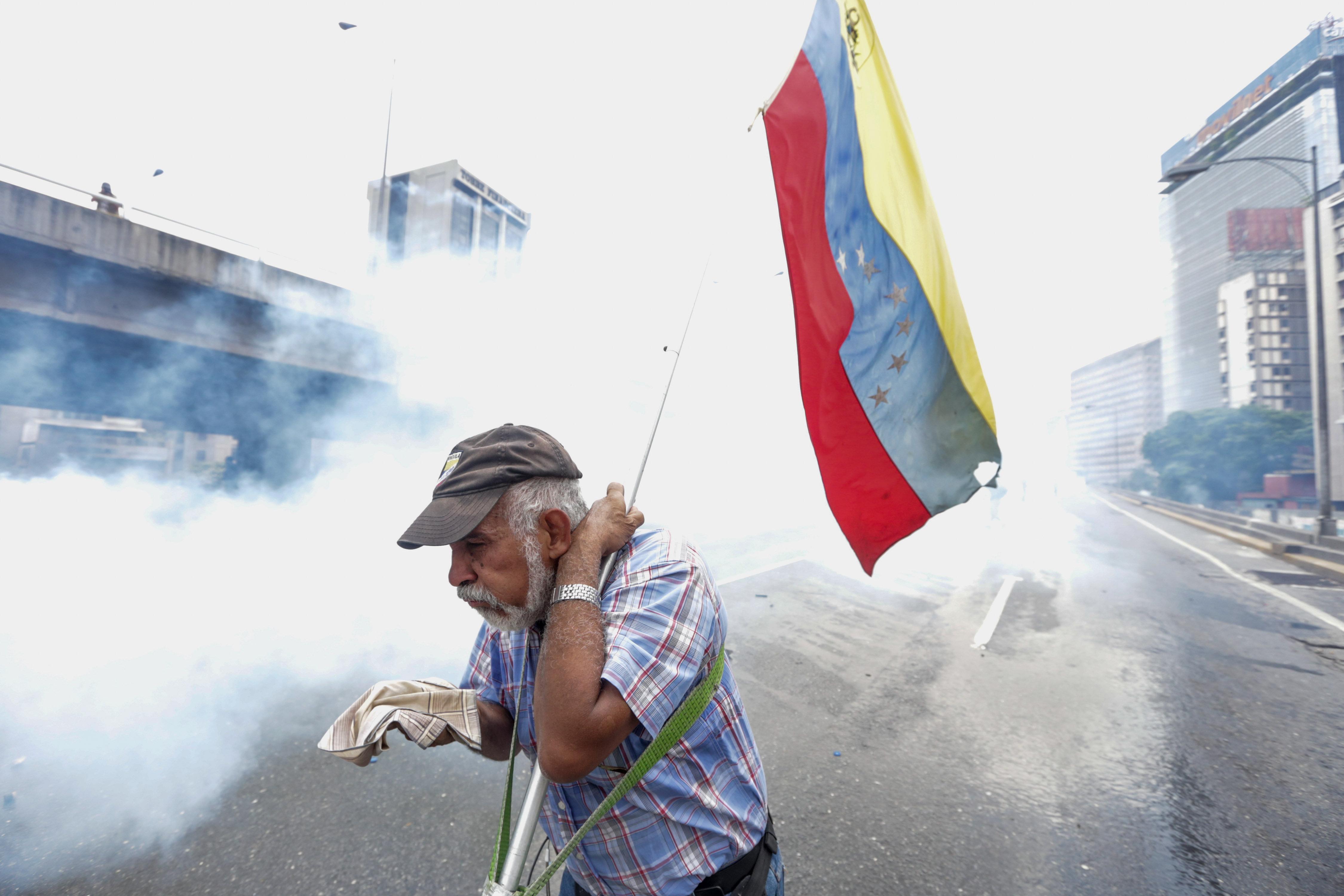 CAR216. CARACAS (VENEZUELA), 19/04/2017 - Un hombre se protege de los gases lacrimógenos durante una protesta contra el Gobierno venezolano hoy, miércoles 19 de abril de 2017, en Caracas (Venezuela). Centenares de opositores en distintos puntos de caracas se enfrentaron hoy a los cuerpos de seguridad para mantenerse en las calles protestando, pese al uso de bombas lacrimógenas por parte de las fuerzas policiales para dispersar y bloquear el paso de las marchas. EFE/CRISTIAN HERNANDEZ