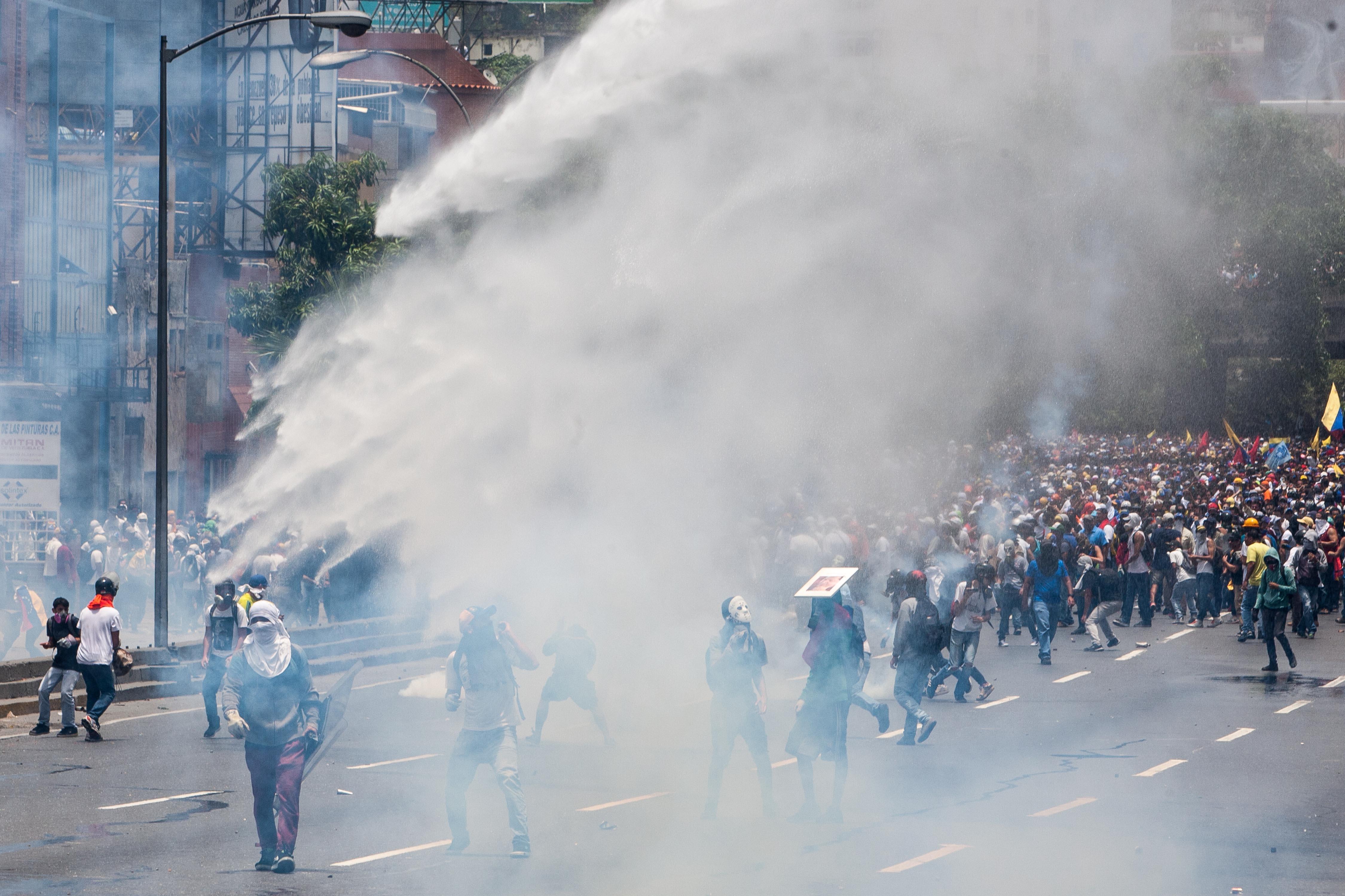 CAR217. CARACAS (VENEZUELA), 19/04/2017 - Un grupo de manifestantes se enfrenta con la policía durante una protesta en contra del Gobierno venezolano hoy, miércoles 19 de abril de 2017, en Caracas (Venezuela). Centenares de opositores en distintos puntos de caracas se enfrentaron hoy a los cuerpos de seguridad para mantenerse en las calles protestando, pese al uso de bombas lacrimógenas por parte de las fuerzas policiales para dispersar y bloquear el paso de las marchas. EFE/CRISTIAN HERNANDEZ