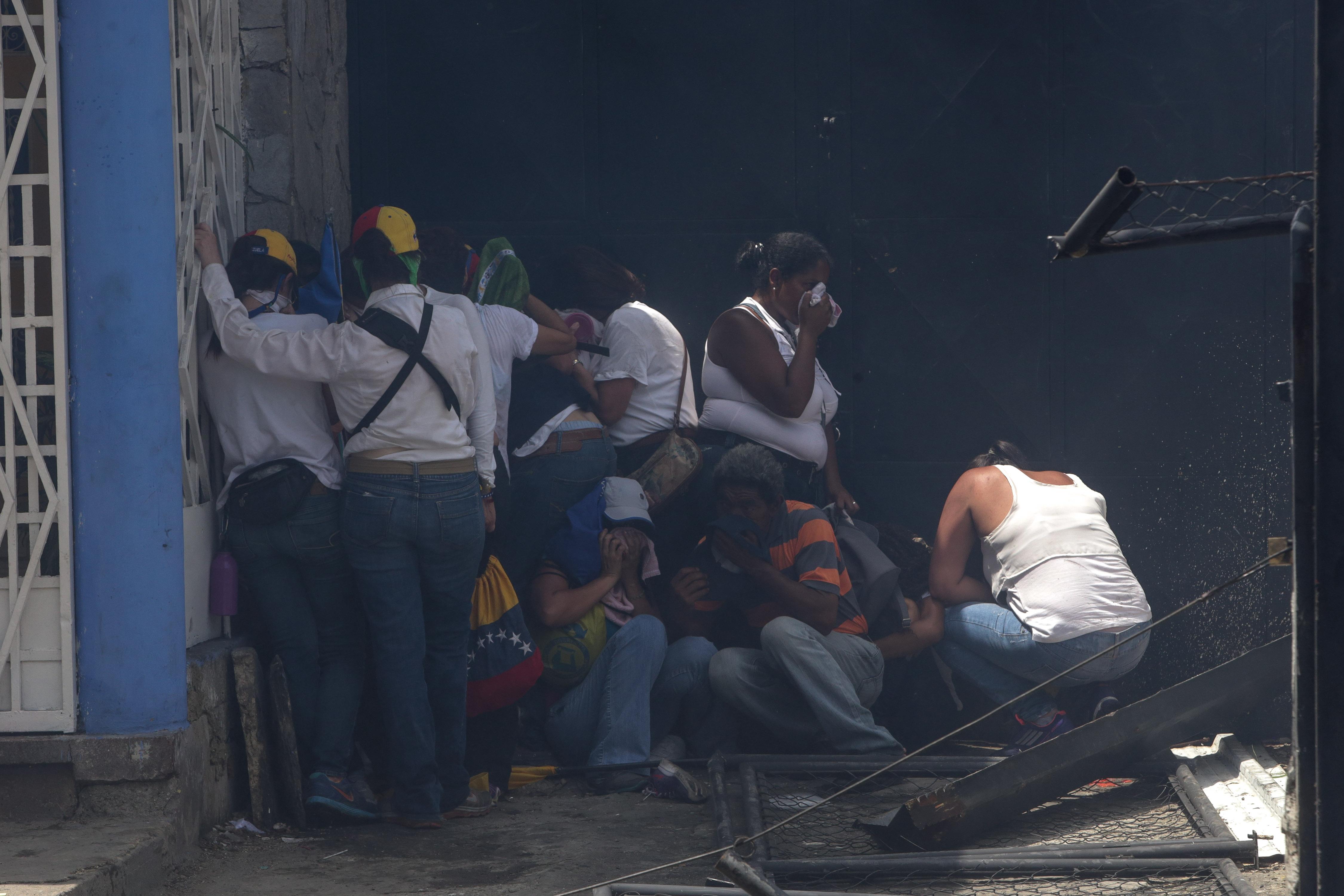 CAR230. CARACAS (VENEZUELA), 19/04/2017 - Un grupo de manifestantes se protege de los gases lacrimógenos durante una protesta en contra del Gobierno venezolano hoy, miércoles 19 de abril de 2017, en Caracas (Venezuela). Centenares de opositores en distintos puntos de caracas se enfrentaron hoy a los cuerpos de seguridad para mantenerse en las calles protestando, pese al uso de bombas lacrimógenas por parte de las fuerzas policiales para dispersar y bloquear el paso de las marchas. EFE/CRISTIAN HERNANDEZ