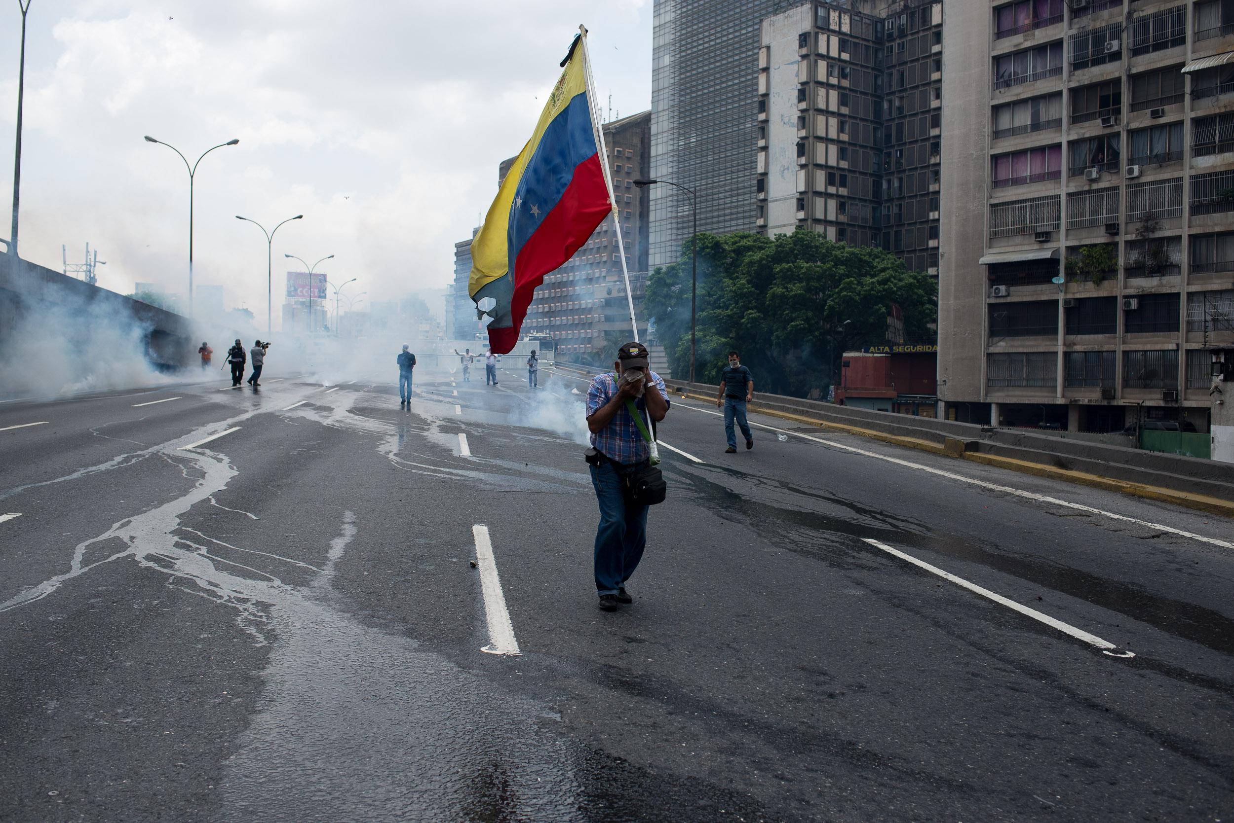 CAR002. CARACAS (VENEZUELA), 19/04/2017.- un grupo de personas se cubre del gas lacrimógeno durante una manifestación opositora que intentaba llegar a la Defensoría del Pueblo hoy, miércoles 19 de abril de 2017, en Caracas (Venezuela.). La policía disolvió hoy con gases lacrimógenos una de las marchas opositoras en el centro de Caracas que pretendía llegar a la sede de la Defensoría del Pueblo, mientras que desde otra de las concentraciones antichavistas en esa zona de la ciudad se reportó una persona muerta. Venezuela es escenario el día de hoy de marchas a favor y en contra del Gobierno a las que cada uno de los bandos ha convocado para medir fuerzas en la calle. EFE/Manaure Quintero
