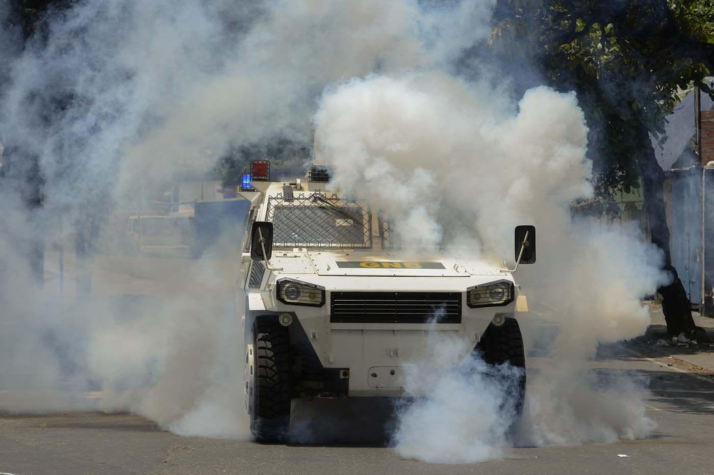 Riot police in an armoured vehicle try to disperse demonstrators during a protest against Venezuelan President Nicolas Maduro, in Caracas on April 20, 2017. Venezuelan riot police fired tear gas Thursday at groups of protesters seeking to oust President Nicolas Maduro, who have vowed new mass marches after a day of deadly unrest. Police in western Caracas broke up scores of opposition protesters trying to join a larger march, though there was no immediate repeat of Wednesday's violent clashes, which left three people dead. / AFP PHOTO / Federico PARRA