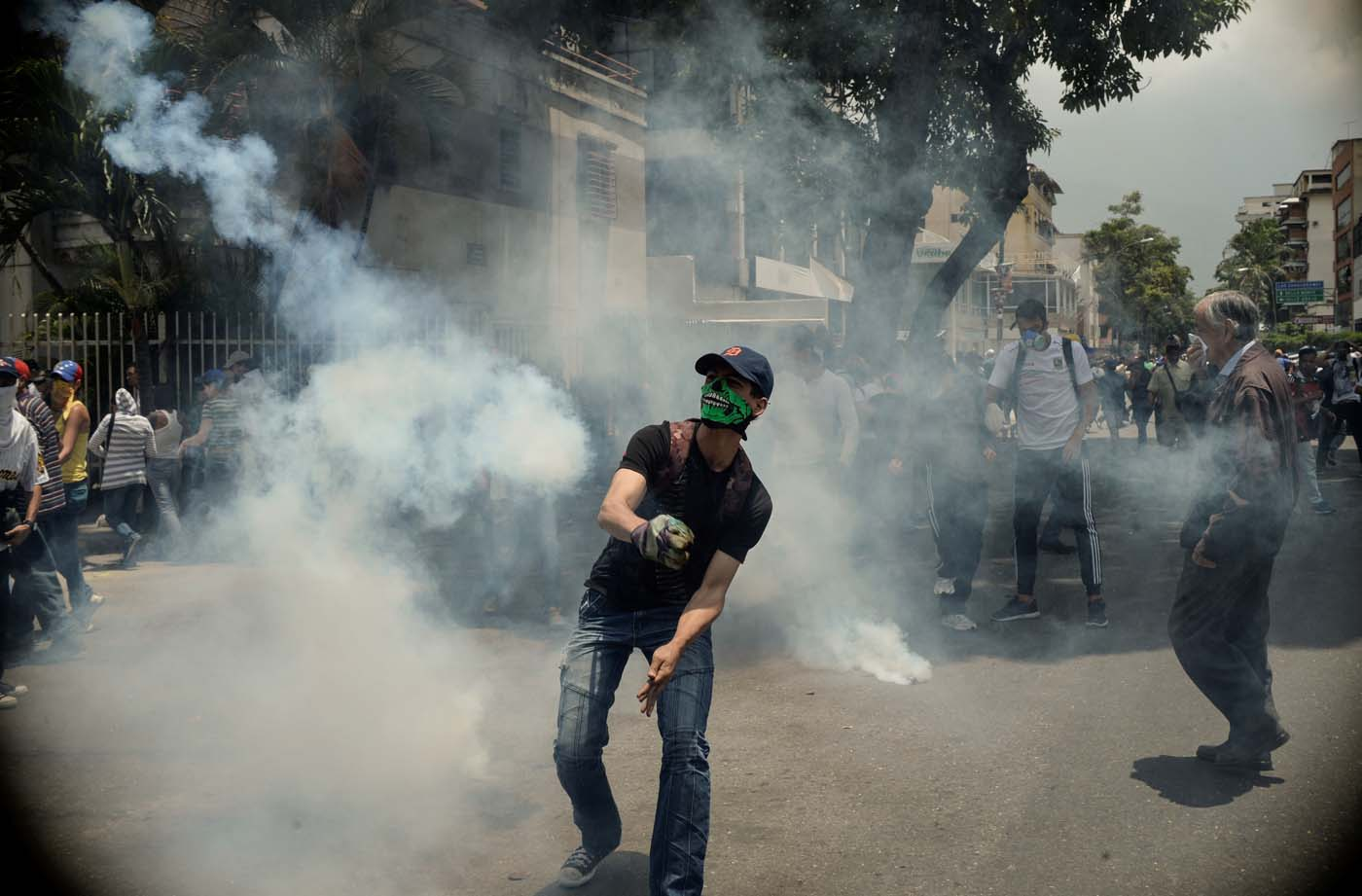 Demonstrators clash with the riot police during a protest against Venezuelan President Nicolas Maduro, in Caracas on April 20, 2017. Venezuelan riot police fired tear gas Thursday at groups of protesters seeking to oust President Nicolas Maduro, who have vowed new mass marches after a day of deadly unrest. Police in western Caracas broke up scores of opposition protesters trying to join a larger march, though there was no immediate repeat of Wednesday's violent clashes, which left three people dead. / AFP PHOTO / Federico PARRA