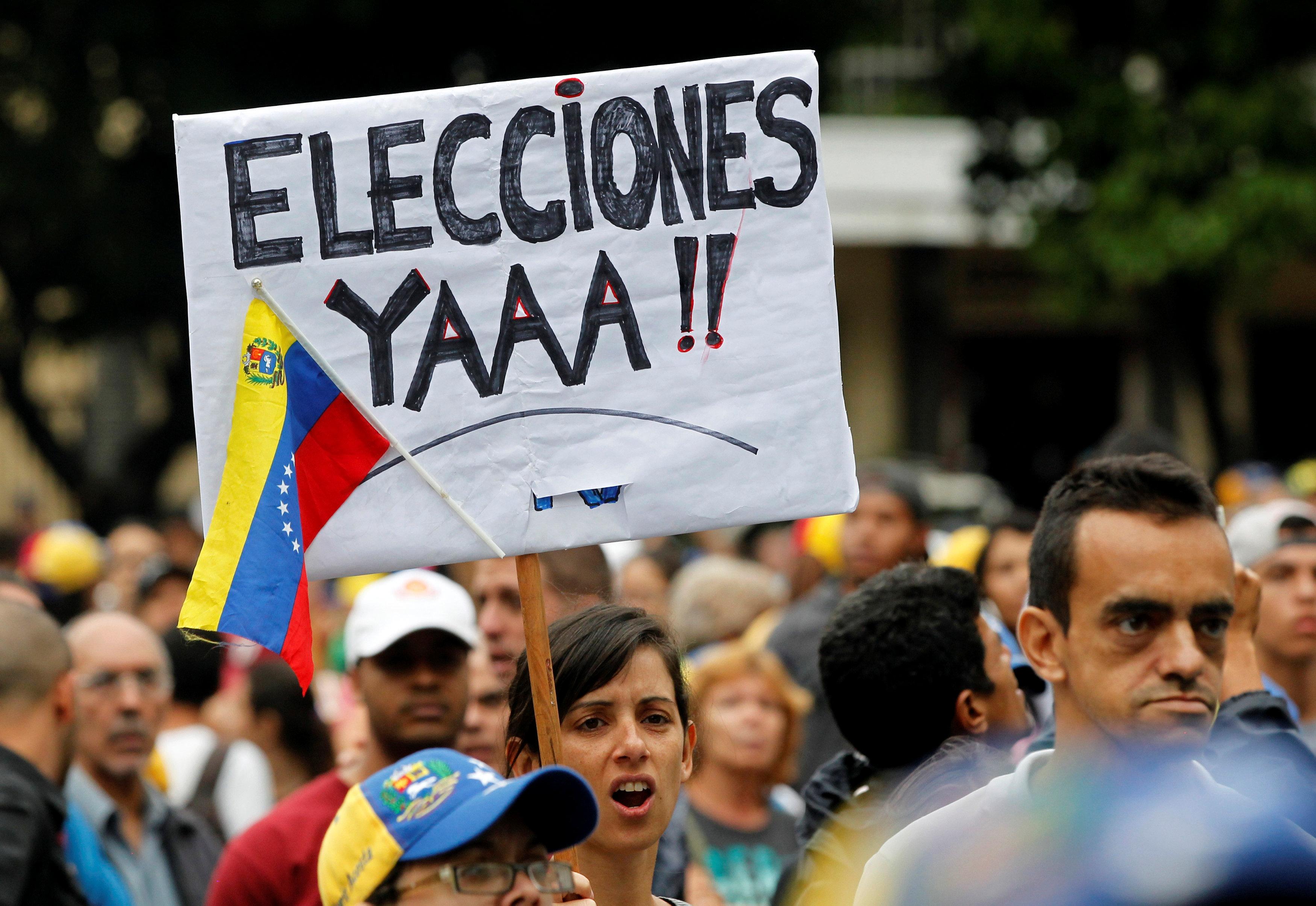 Manifestante lleva un cartel que dice