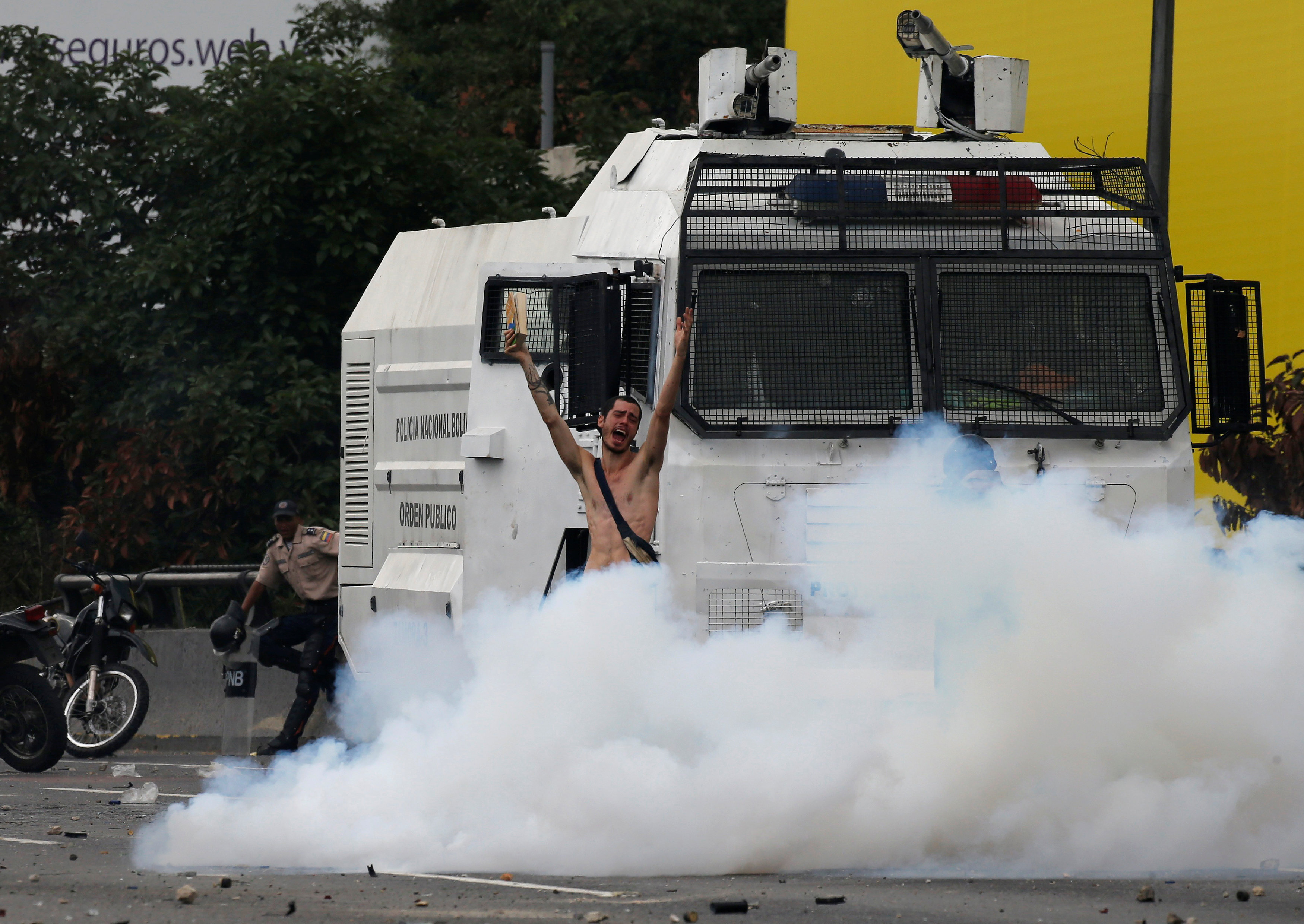 A naked demonstrator reacts amidst tear gas during clashes with police during a rally against Venezuela's President Nicolas Maduro in Caracas, Venezuela, April 20, 2017. REUTERS/Carlos Garcia RawlinsTEMPLATE OUT