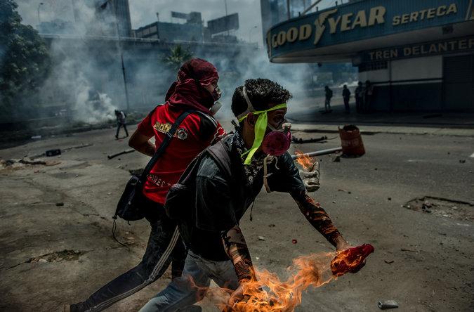 Jóvenes lanzan bombas molotov contra las fuerzas de seguridad, el miércoles en Caracas. Credit Meridith Kohut para The New York Times