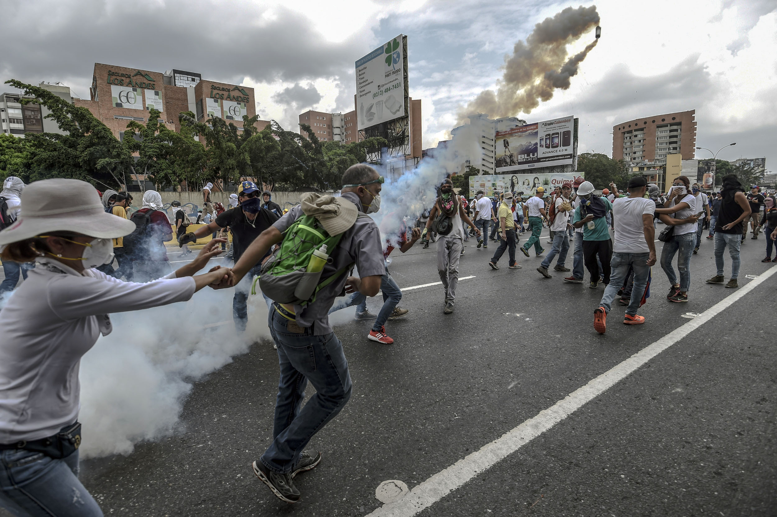 Demonstrators clash with riot police during a protest against Venezuelan President Nicolas Maduro, in Caracas on April 20, 2017. Venezuelan riot police fired tear gas Thursday at groups of protesters seeking to oust President Nicolas Maduro, who have vowed new mass marches after a day of deadly unrest. Police in western Caracas broke up scores of opposition protesters trying to join a larger march, though there was no immediate repeat of Wednesday's violent clashes, which left three people dead. / AFP PHOTO / JUAN BARRETO