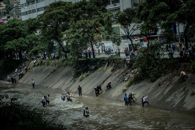 Manifestantes escapan de las bombas lacrimógenas el miércoles lanzándose al Guaire, un río contaminado en Caracas. Credit Meridith Kohut para The New York Times