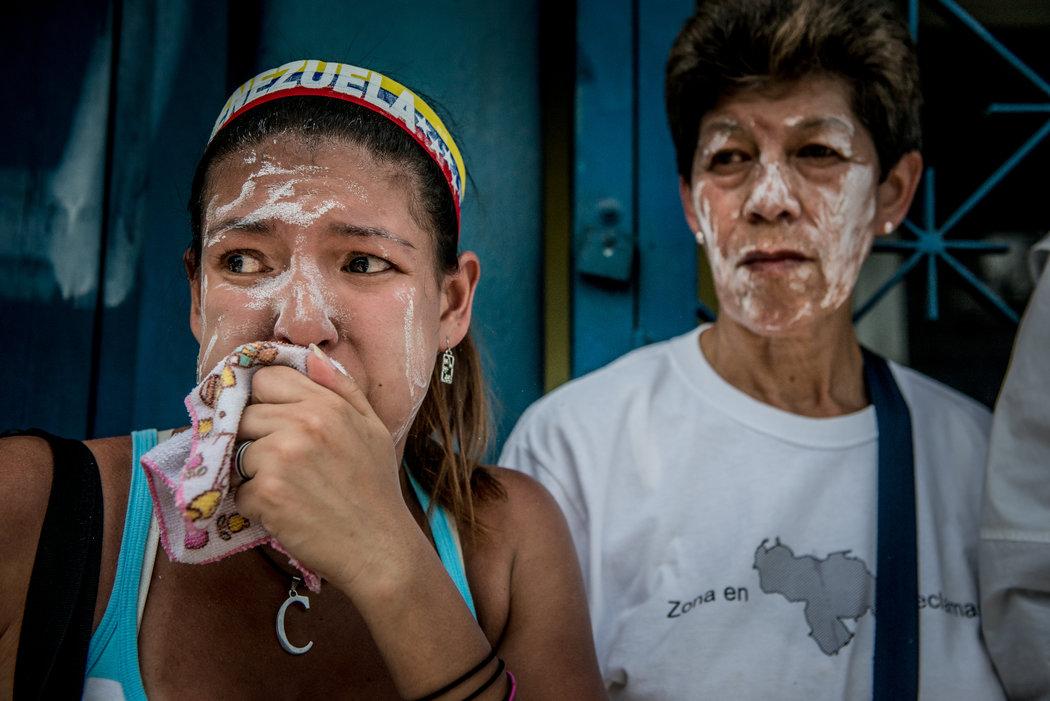 Manifestantes se recuperan de los gases lacrimógenos lanzados por los cuerpos de seguridad durante una marcha multitudinaria, el miércoles en Caracas. Credit Meridith Kohut para The New York Times