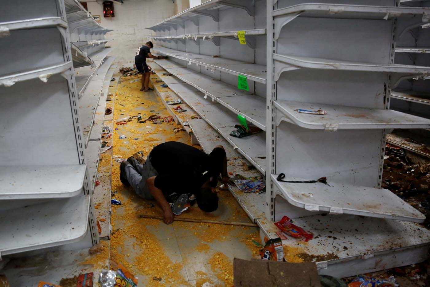 Workers look for valuables among the damaged goods in a supermarket, after it was looted in Caracas, Venezuela April 21, 2017. REUTERS/Carlos Garcia Rawlins