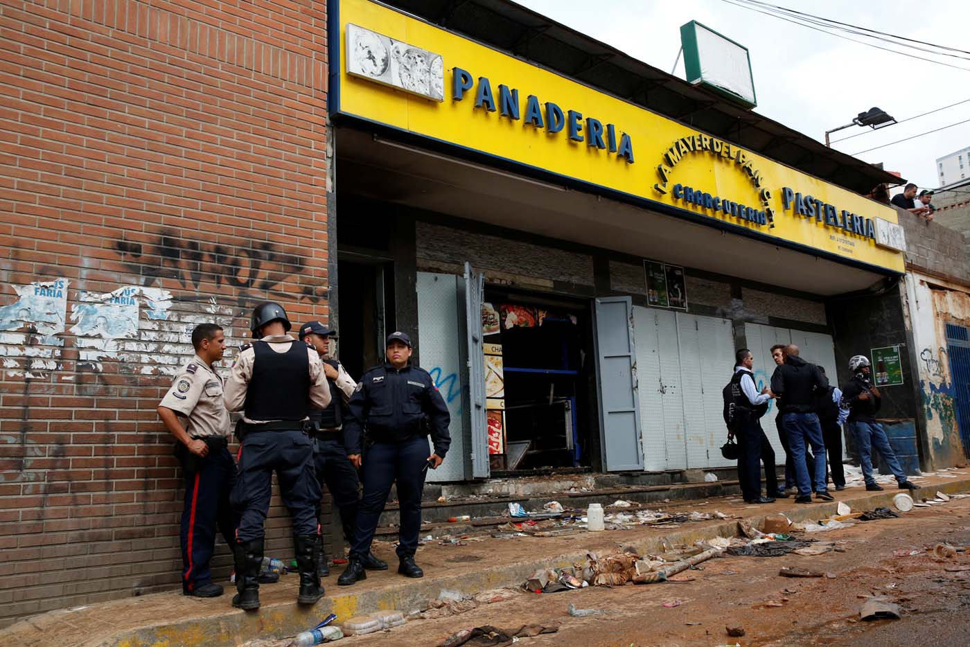 Police officers and criminal investigators stand in front of a bakery, after it was looted in Caracas, Venezuela April 21, 2017. REUTERS/Carlos Garcia Rawlins