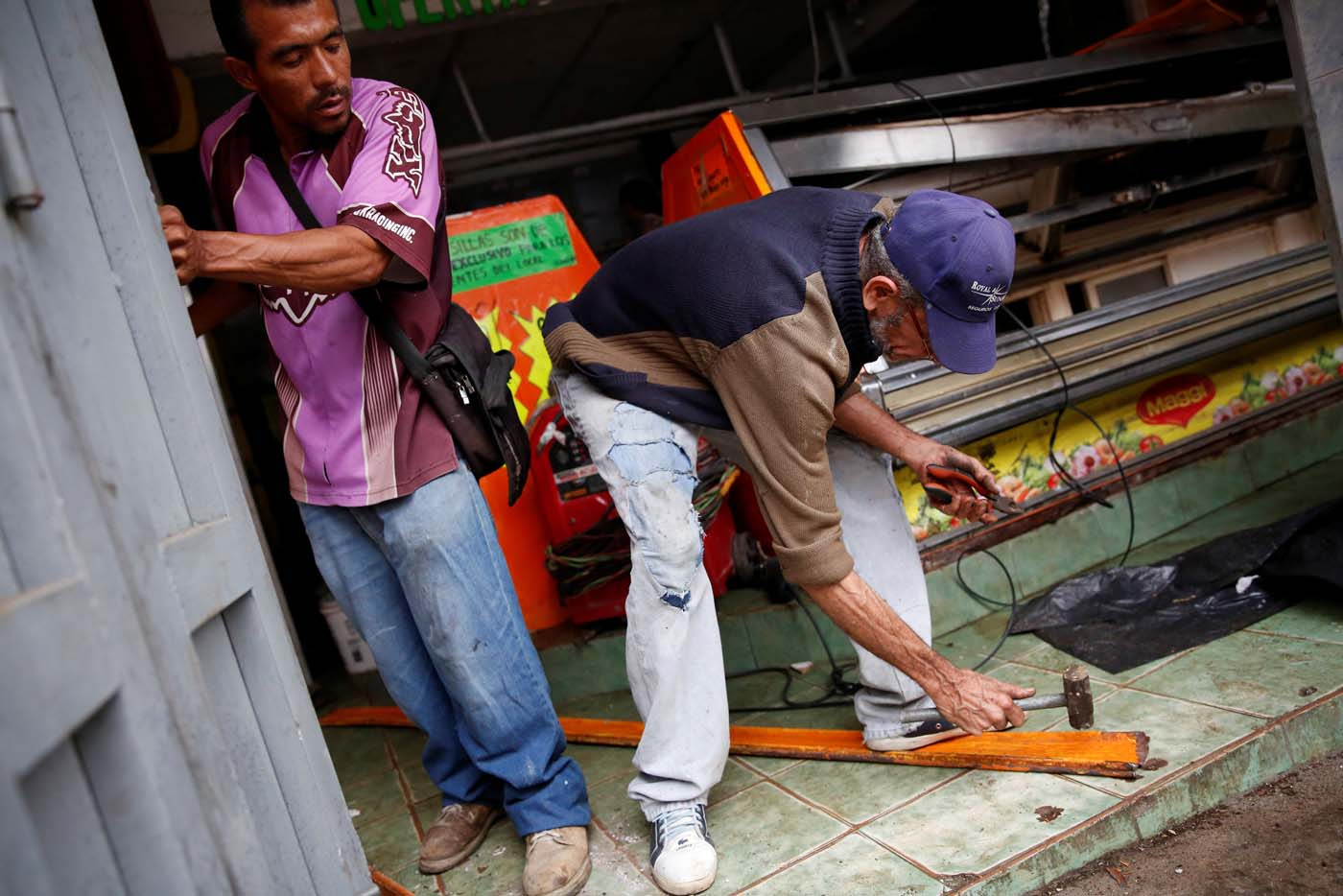 Workers try to repair the broken doors of a butcher's stall after it was looted in Caracas, Venezuela April 21, 2017. REUTERS/Carlos Garcia Rawlins