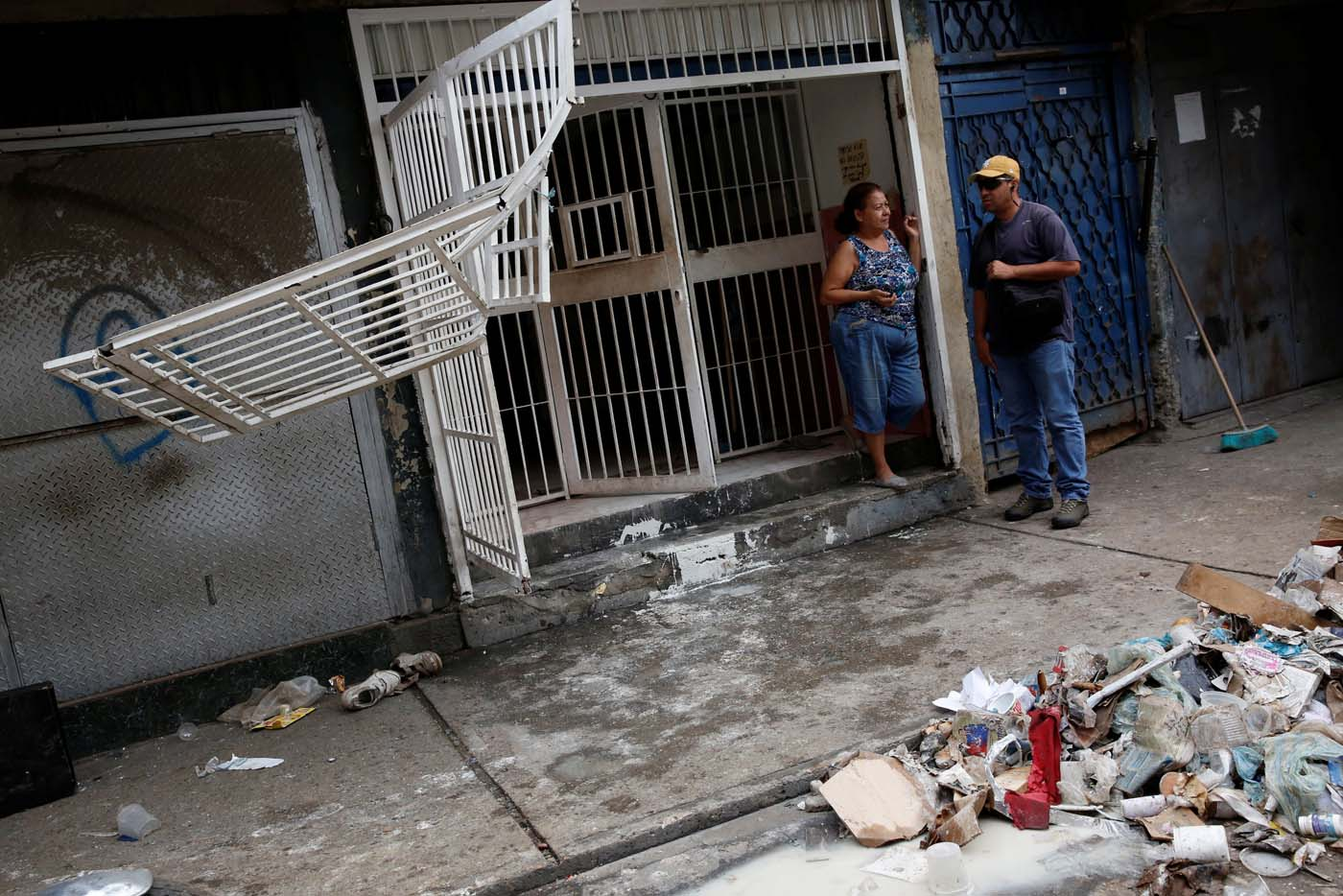 People talk next to the broken fences of a stall after it was looted in Caracas, Venezuela April 21, 2017. REUTERS/Carlos Garcia Rawlins