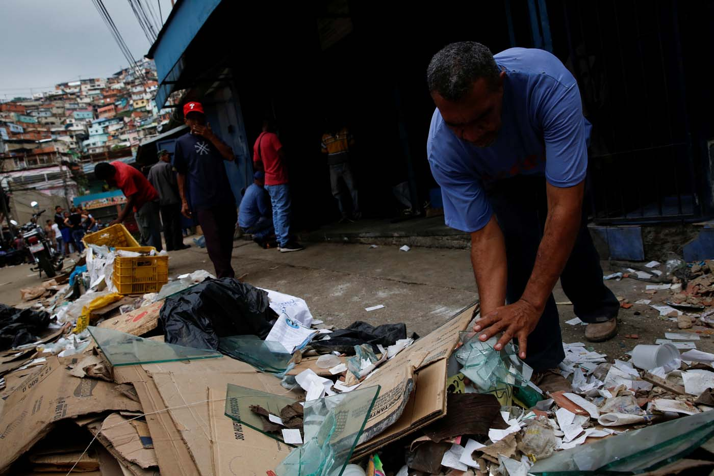 A man discards broken glass, while he tries to cleans his stall at a commercial street, after it was looted in Caracas, Venezuela April 21, 2017. REUTERS/Carlos Garcia Rawlins