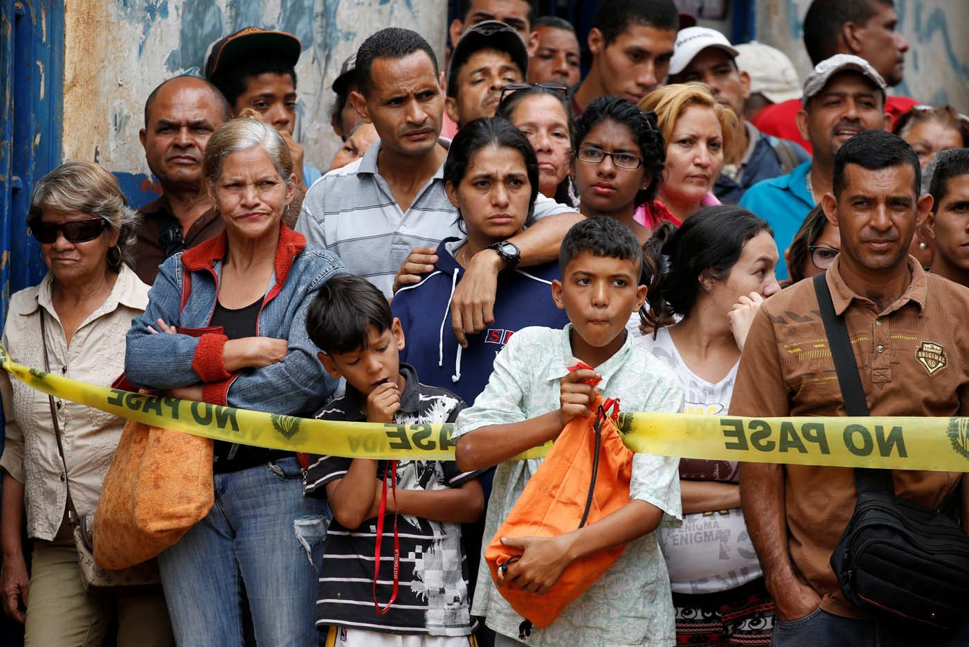 People look at police officers and criminal investigators while they collect evidence in front of a bakery, after it was looted in Caracas, Venezuela April 21, 2017. REUTERS/Carlos Garcia Rawlins TPX IMAGES OF THE DAY