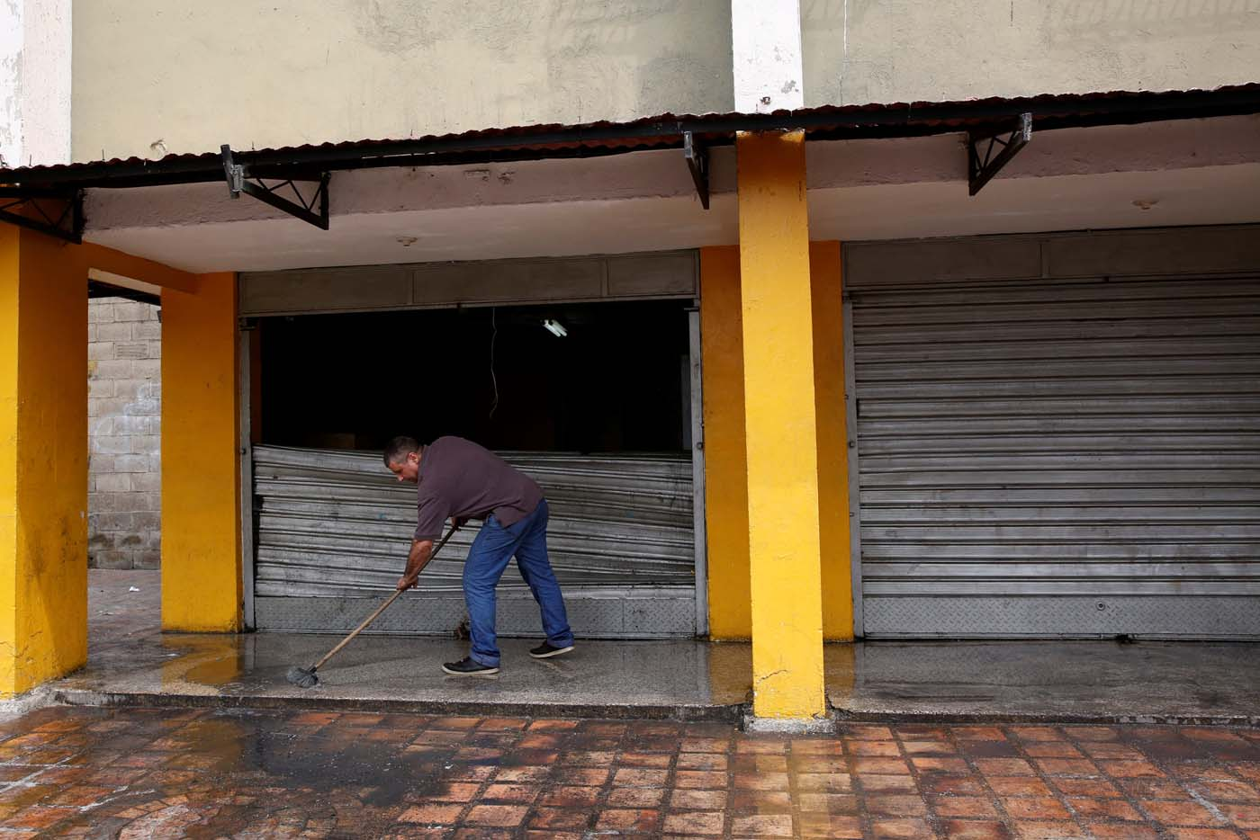 A man cleans the floor next to the broken door of a supermarket which was looted in Caracas, Venezuela April 21, 2017. REUTERS/Carlos Garcia Rawlins