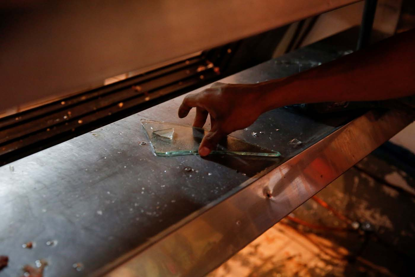 A man grabs pieces of glass from a broken refrigerator after a butcher's stall was looted in Caracas, Venezuela April 21, 2017. REUTERS/Carlos Garcia Rawlins