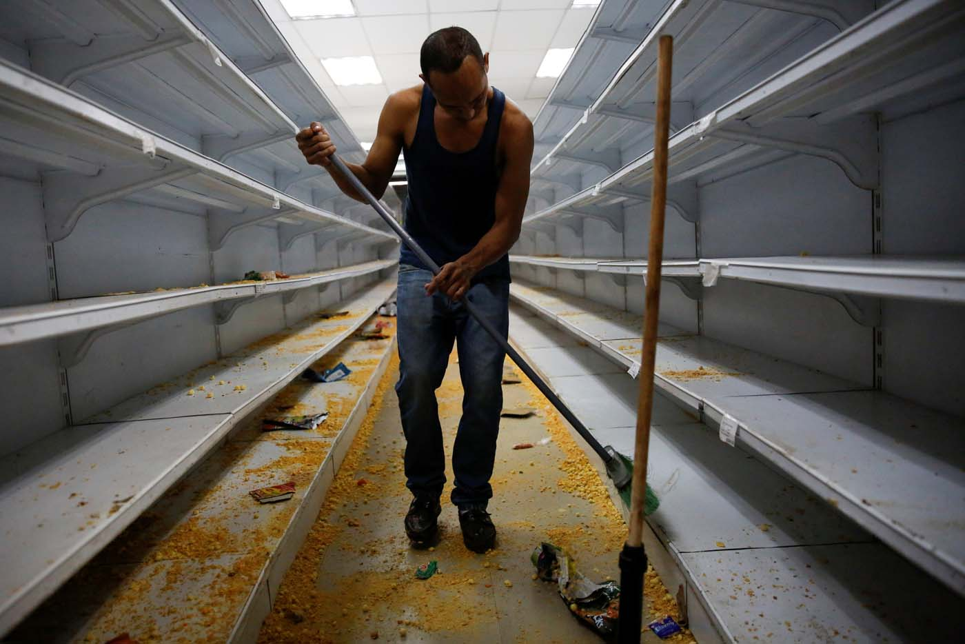 A worker cleans the shelves in a supermarket after it was looted in Caracas, Venezuela April 21, 2017. REUTERS/Carlos Garcia Rawlins