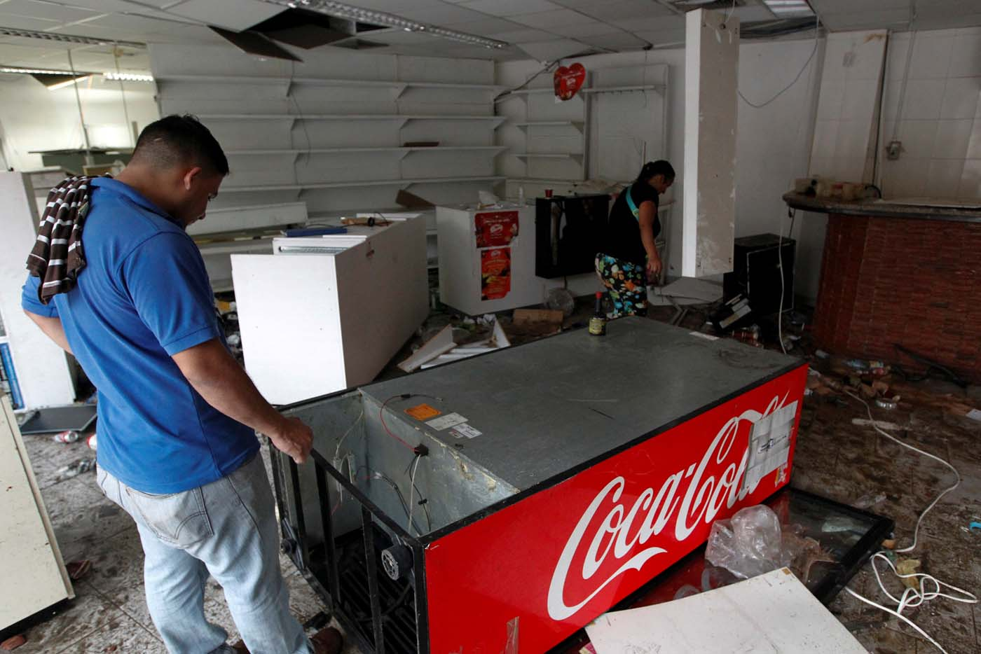 A worker looks for valuables scattered in the damaged goods in a convenience store, after it was looted in Caracas, Venezuela April 21, 2017. REUTERS/Christian Veron