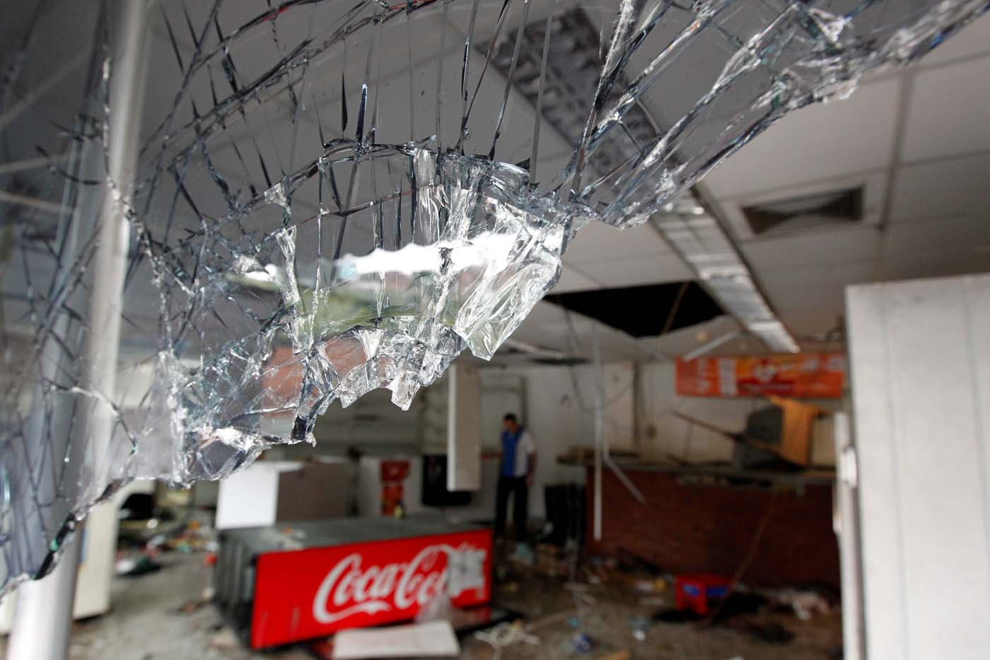 Broken glass is seen in a convenience store, after it was looted in Caracas, Venezuela April 21, 2017. REUTERS/Christian Veron