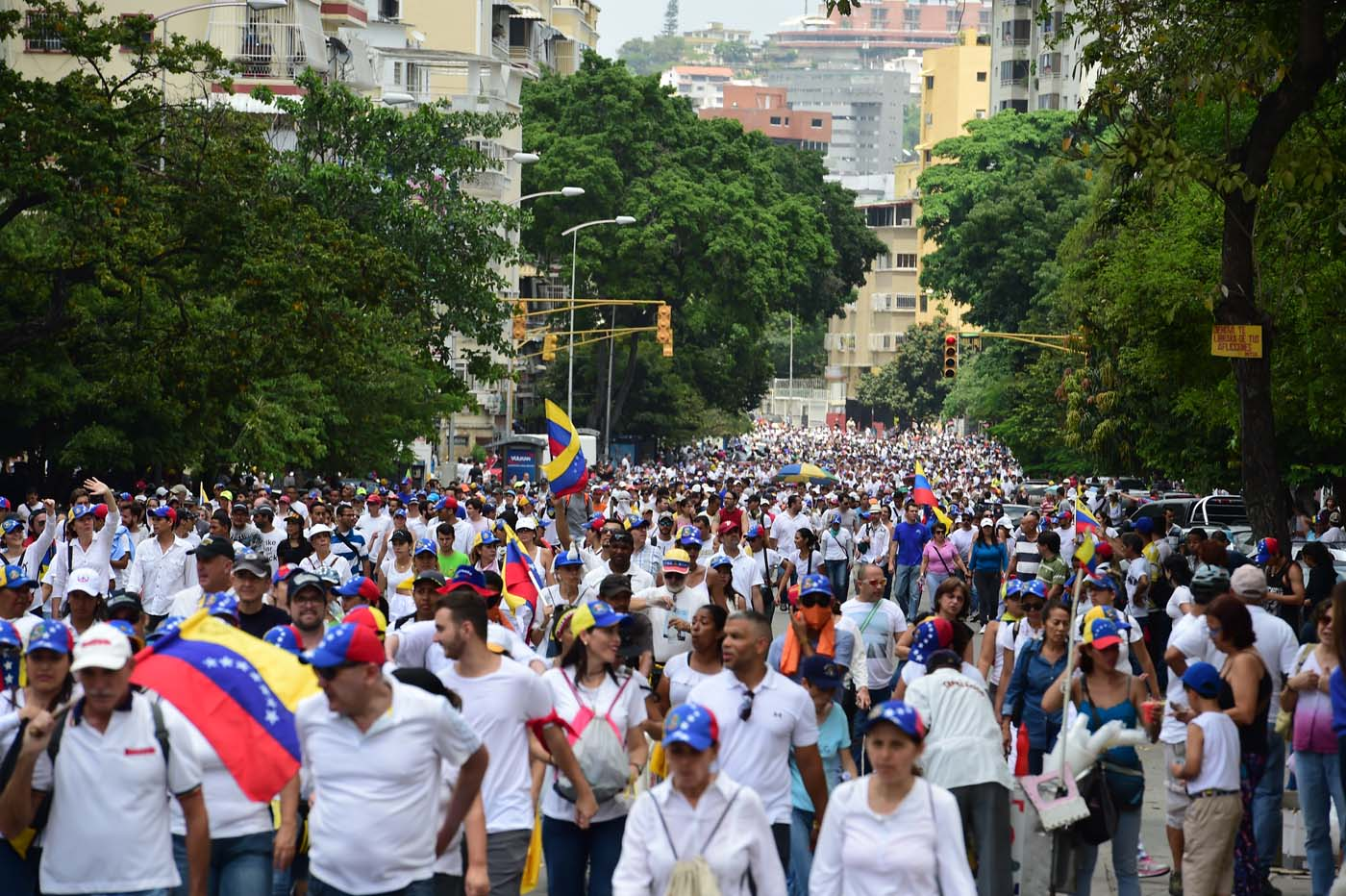 "Opposition activists march towards the Catholic Church's episcopal seats nationwide, in Caracas, on April 22, 2017. Venezuelans gathered Saturday for ""silent marches"" against President Nicolas Maduro, a test of his government's tolerance for peaceful protests after three weeks of violent unrest that has left 20 people dead. / AFP PHOTO / RONALDO SCHEMIDT"