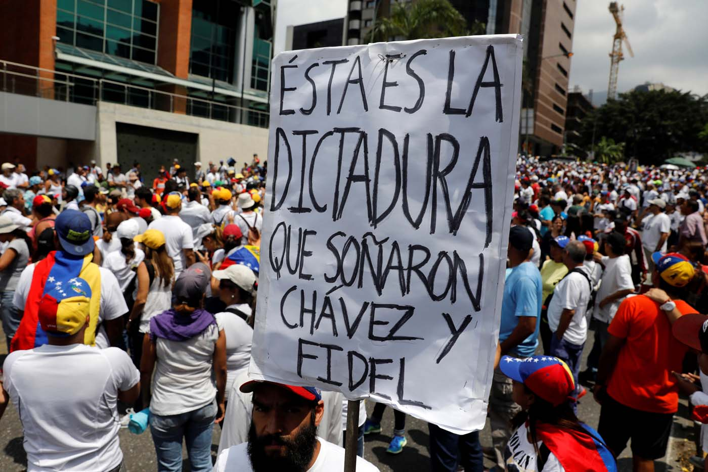 """A demonstrator holds a placard as he takes part in a rally to honour victims of violence during a protest against Venezuela's President Nicolas Maduro's government in Caracas, Venezuela, April 22, 2017. The placard reads """"This is the dictatorship who dreamed, Chavez and Fidel"""". REUTERS/Carlos Garcia Rawlins"""
