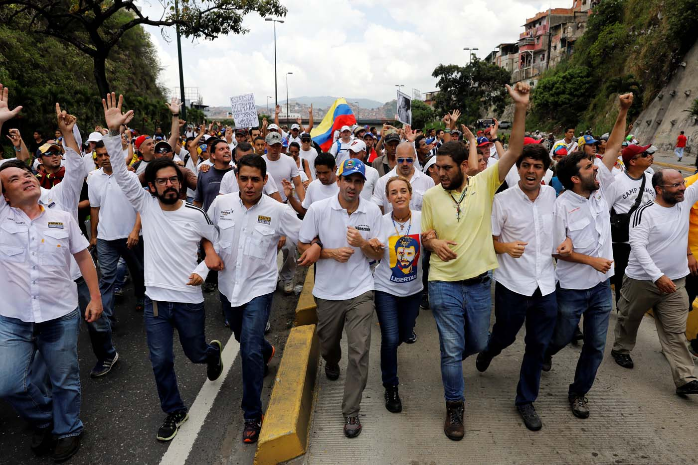 Venezuelan opposition leader and Governor of Miranda state Henrique Capriles (4th L), Lilian Tintori, (5th R), wife of jailed opposition leader Leopoldo Lopez, walk together with lawmakers as they take part in a rally to honour victims of violence during a protest against Venezuela's President Nicolas Maduro's government in Caracas, Venezuela, April 22, 2017. REUTERS/Carlos Garcia Rawlins