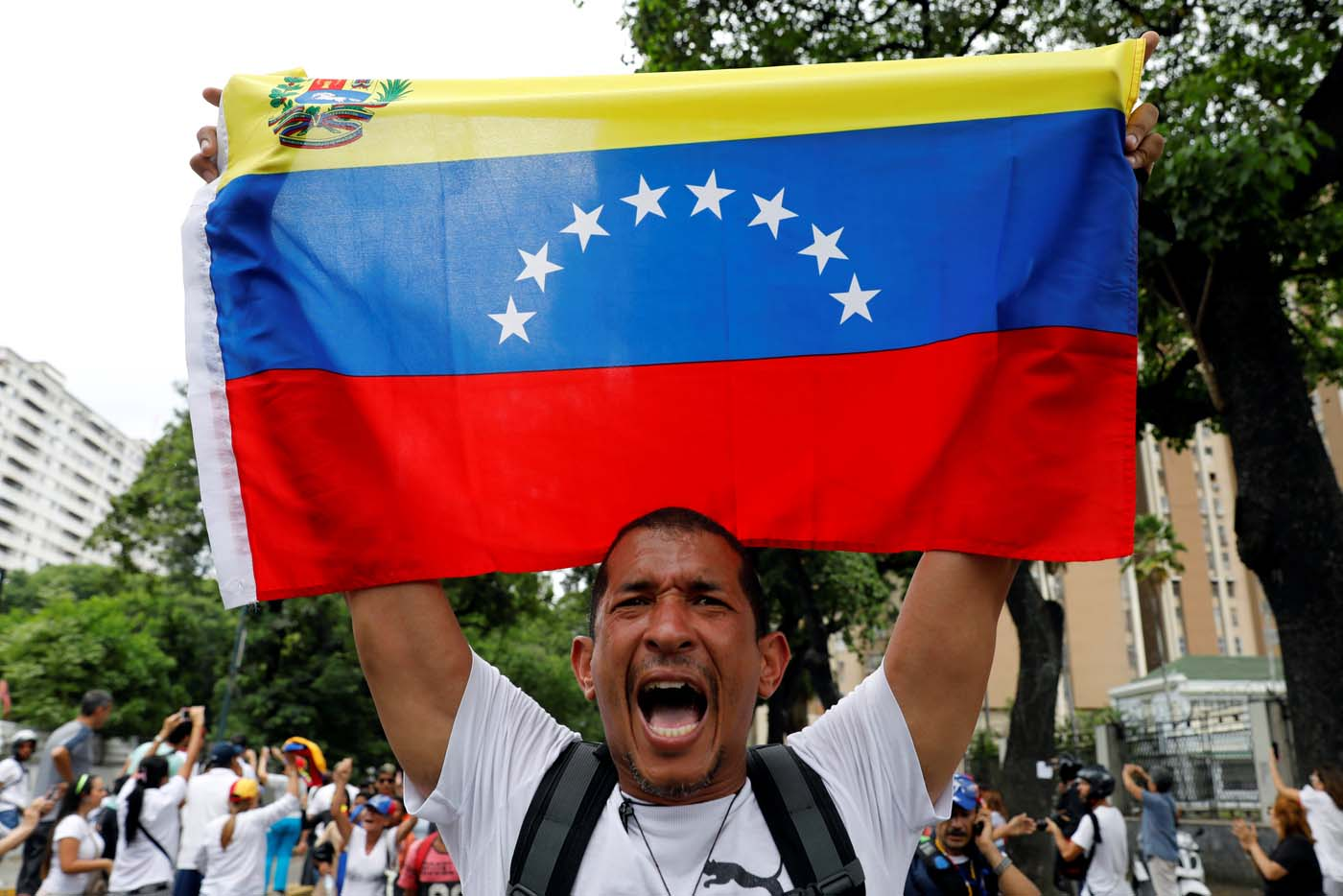 A demonstrator holds a Venezuelan flag as he takes part in a rally to honour victims of violence during a protest against Venezuela's President Nicolas Maduro's government in Caracas, Venezuela, April 22, 2017. REUTERS/Carlos Garcia Rawlins TPX IMAGES OF THE DAY