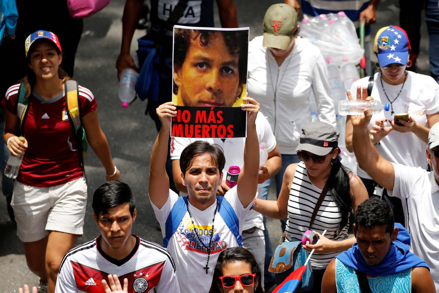 """A demonstrator holds a picture as he takes part in a rally to honour victims of violence during a protest against Venezuela's President Nicolas Maduro's government in Caracas, Venezuela, April 22, 2017. Picture reads, """"No more deaths"""". REUTERS/Carlos Garcia Rawlins"""