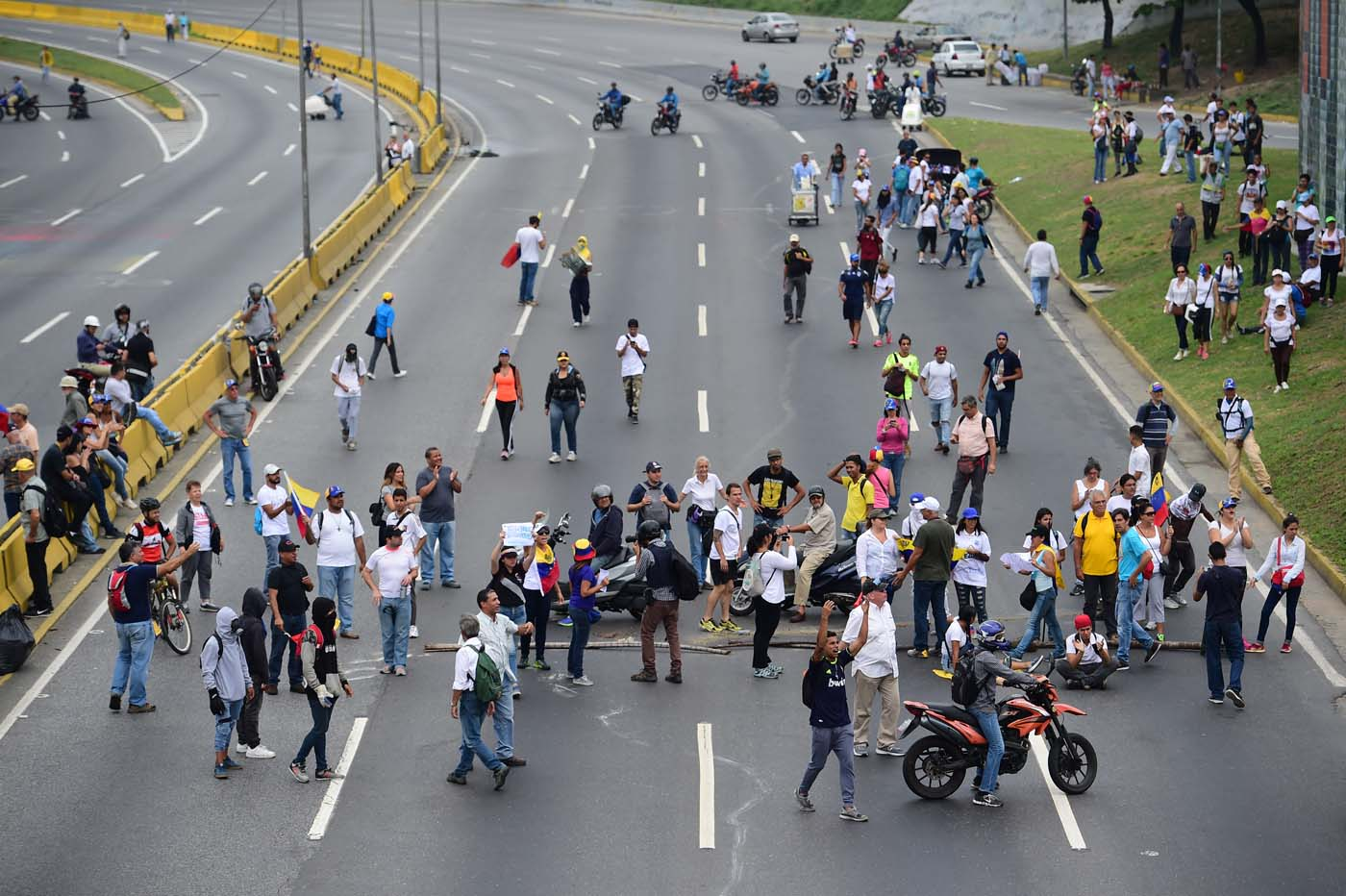Venezuelan opposition activists block the Francisco Fajardo motorway in Caracas, on April 24, 2017. Protesters plan Monday to block Venezuela's main roads including the capital's biggest motorway, triggering fears of further violence after three weeks of unrest left 21 people dead. / AFP PHOTO / RONALDO SCHEMIDT