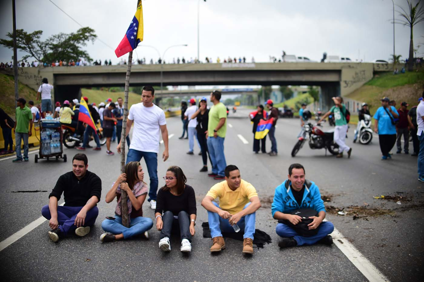 Venezuelan opposition activists block organize a sit-in to block the Francisco Fajardo motorway in Caracas, on April 24, 2017. Protesters plan Monday to block Venezuela's main roads including the capital's biggest motorway, triggering fears of further violence after three weeks of unrest left 21 people dead. / AFP PHOTO / RONALDO SCHEMIDT
