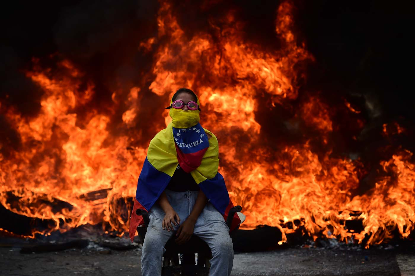 A Venezuelan opposition activist is backdropped by a burning barricade during a demonstration against President Nicolas Maduro in Caracas, on April 24, 2017. Protesters rallied on Monday vowing to block Venezuela's main roads to raise pressure on Maduro after three weeks of deadly unrest that have left 21 people dead. Riot police fired rubber bullets and tear gas to break up one of the first rallies in eastern Caracas early Monday while other groups were gathering elsewhere, the opposition said.  / AFP PHOTO / Ronaldo SCHEMIDT