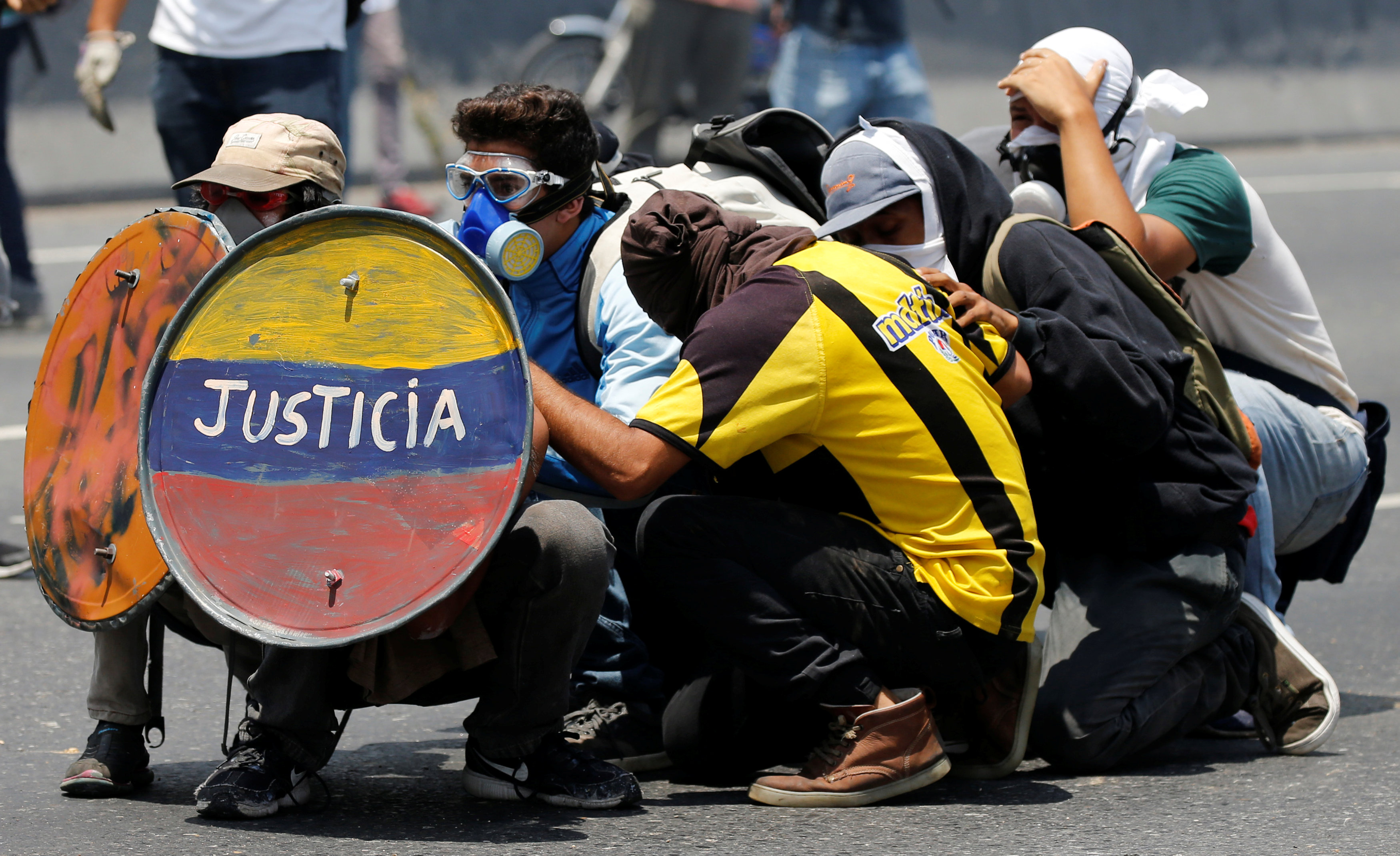 """Opposition supporters use a shield reading """"Justice"""" as they clash with security forces during a rally against Venezuela's President Nicolas Maduro in Caracas, Venezuela April 26, 2017. REUTERS/Carlos Garcia Rawlins"""