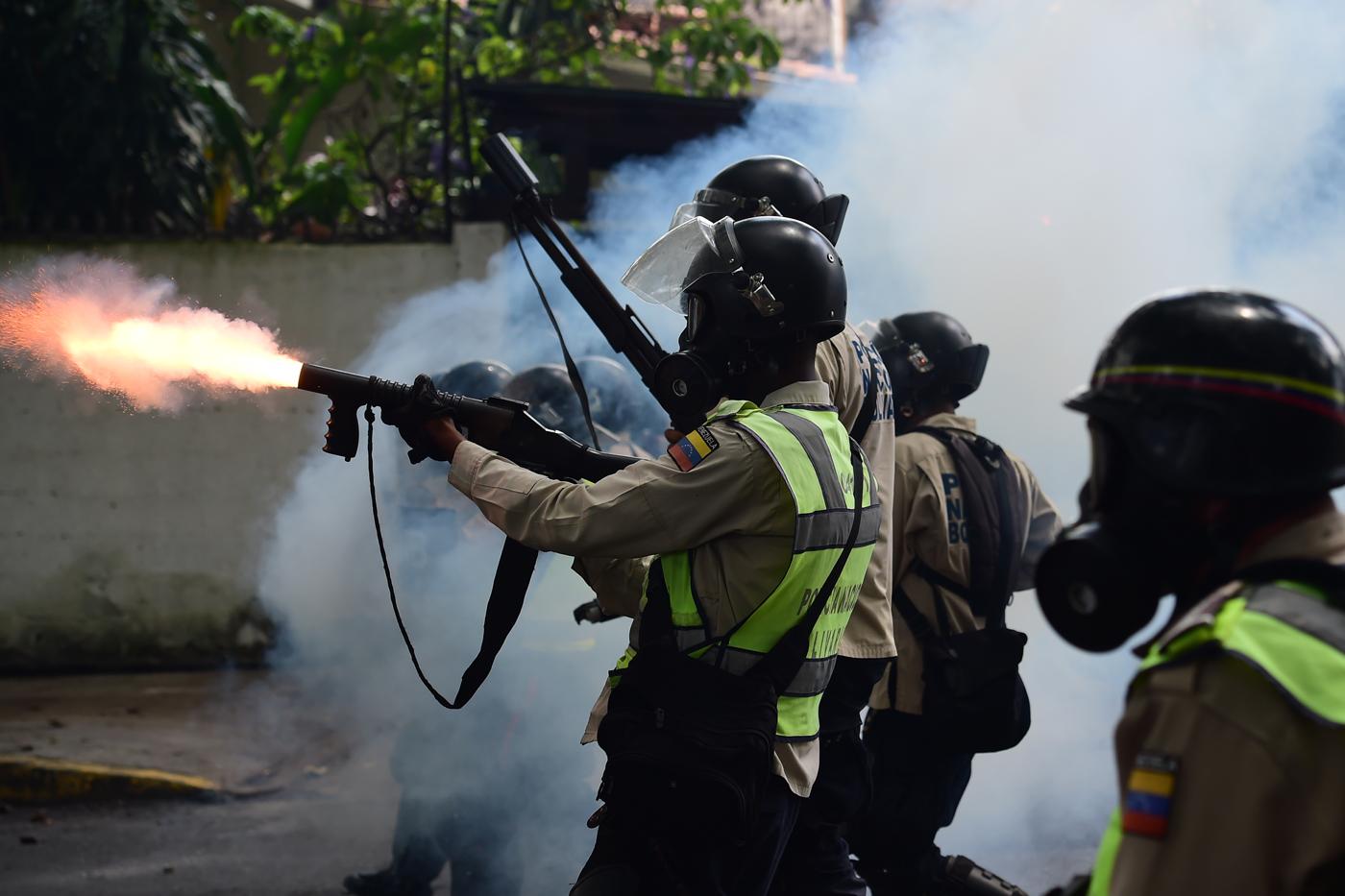 Oficial de la PNB disparando bomba lacrimógena en dirección a manifestantes opositores en la avenida La Victoria el lunes 1 de mayor de 2017. Foto: AFP