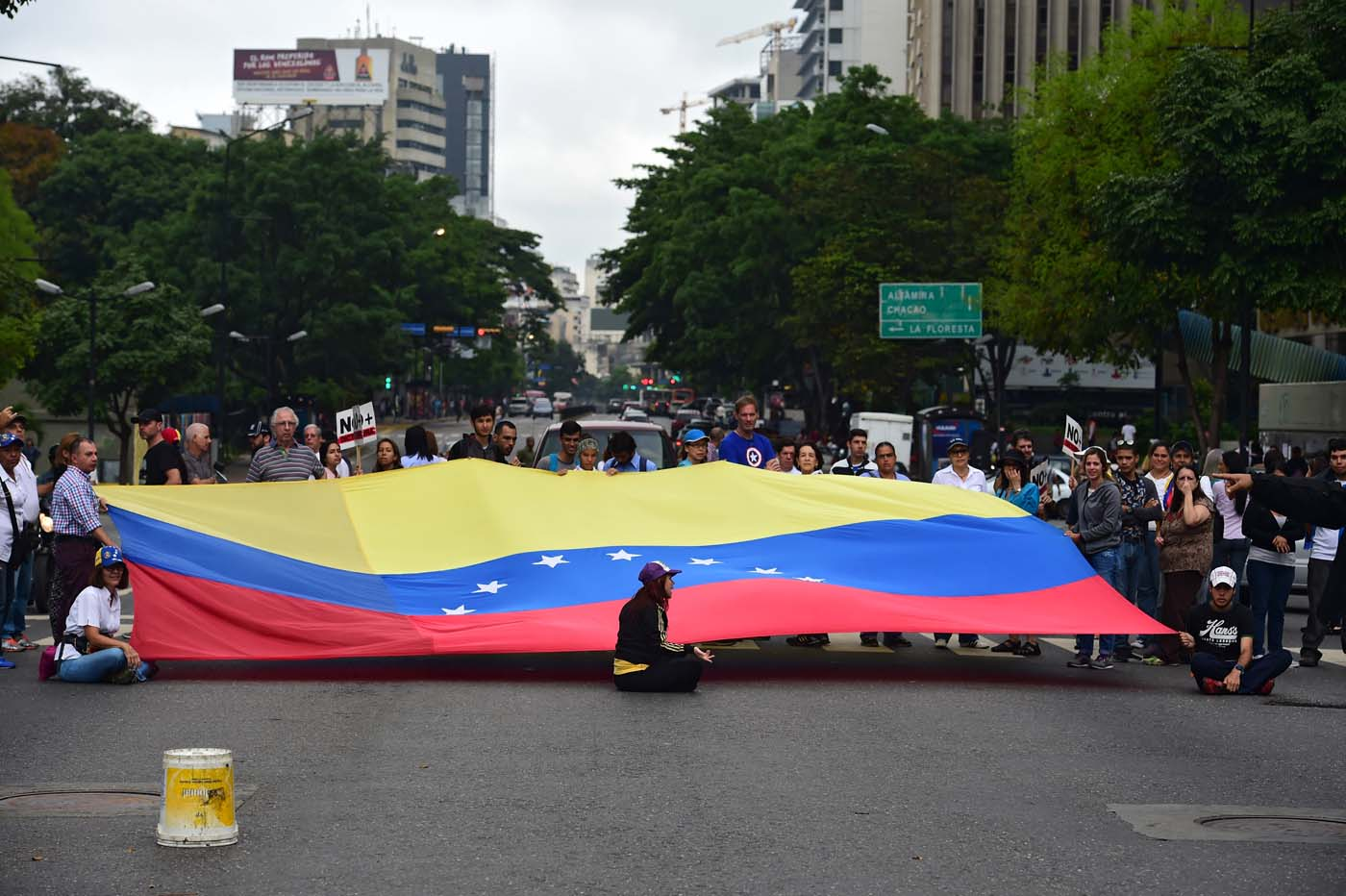 "Demonstrators display a Venezuelan national flag as they block a street during a protest against Venezuelan President Nicolas Maduro in Caracas, on May 2, 2017. Venezuelan President Nicolas Maduro called for a new constitution Monday as he fights to quell a crisis that has led to more than a month of protests against him and deadly street violence. The opposition slammed the tactic as a ""coup d'etat"" and urged protesters to ""block the streets"" from Tuesday. It said it was organizing a ""mega protest"" for Wednesday. / AFP PHOTO / RONALDO SCHEMIDT"