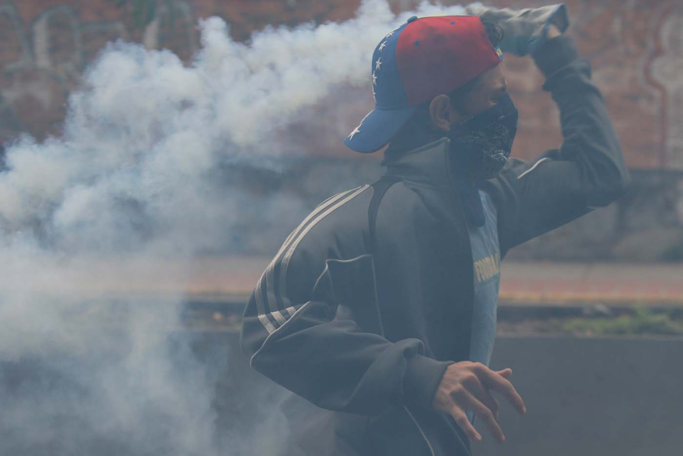 A demonstrator throws back a tear gas canister during a protest against Venezuela's President Nicolas Maduro's government in Caracas, Venezuela May 2, 2017. REUTERS/Carlos Garcia Rawlins