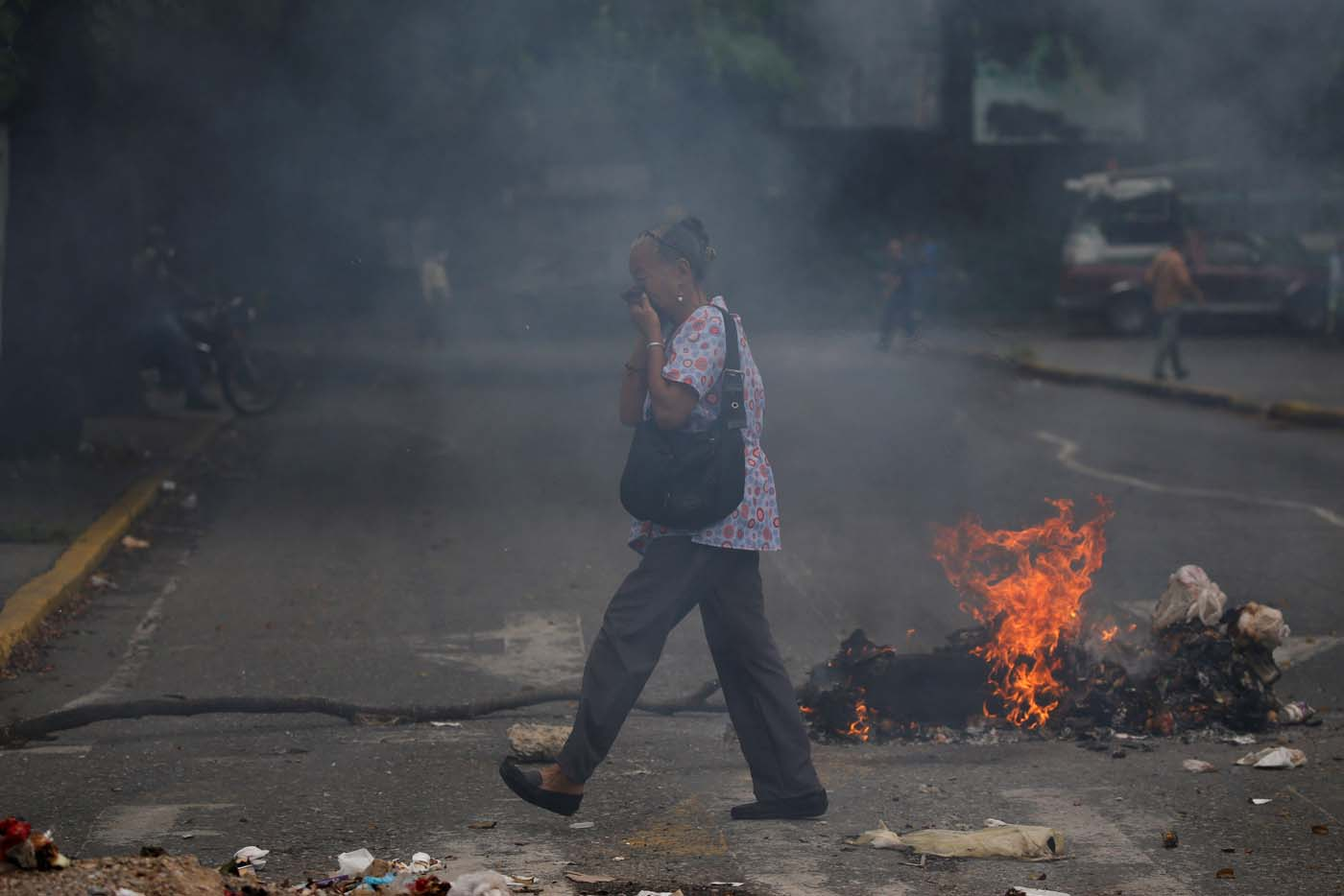 A woman covers her face as she walks past a burning barricade during a protest against Venezuela's President Nicolas Maduro's government in Caracas, Venezuela May 2, 2017. REUTERS/Carlos Garcia Rawlins