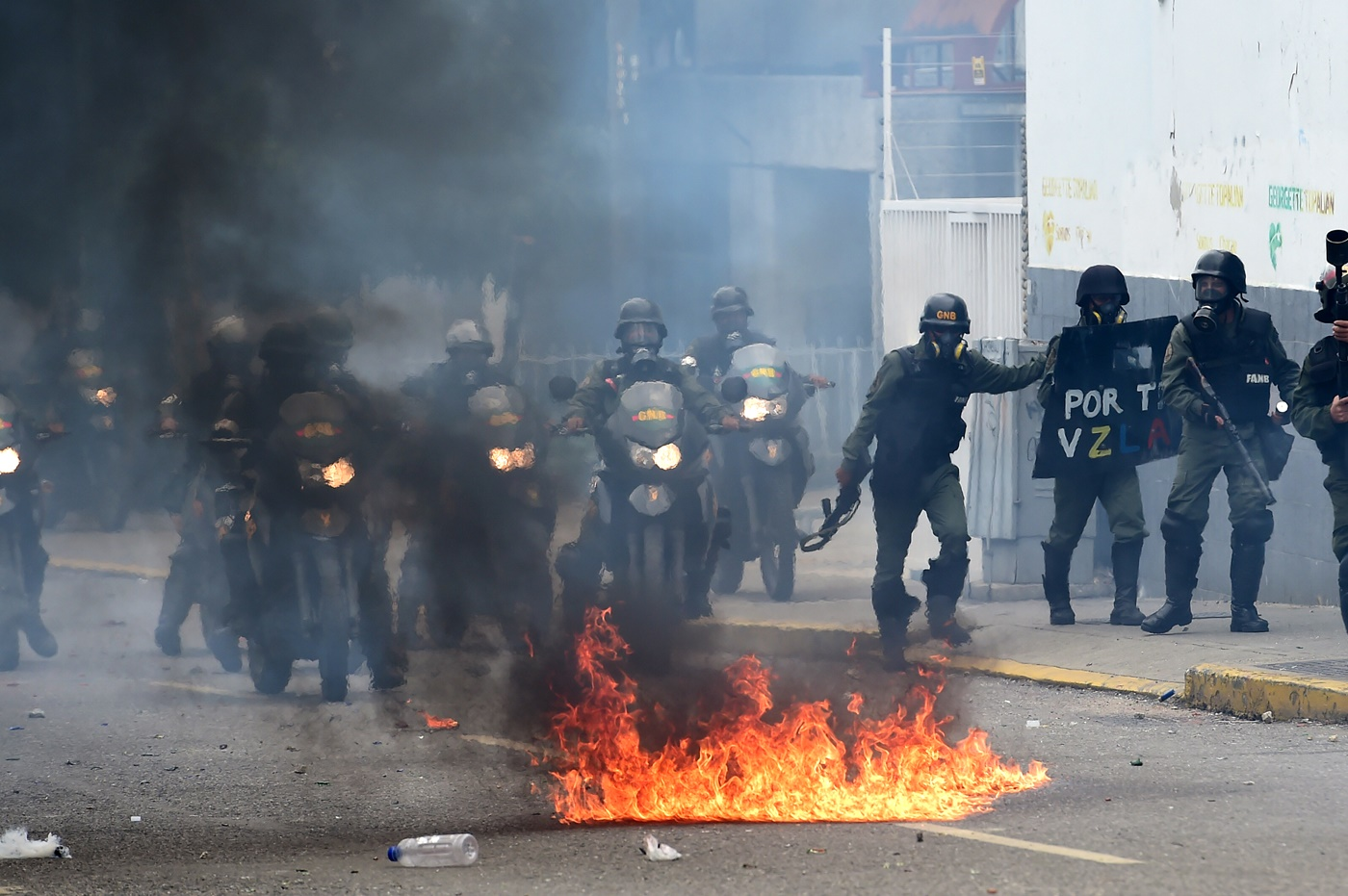 Venezuelan National Guard personnel in riot gear clash with opposition demonstrators during a protest against Venezuelan President Nicolas Maduro, in Caracas on May 3, 2017. Venezuela's angry opposition rallied Wednesday vowing huge street protests against President Nicolas Maduro's plan to rewrite the constitution and accusing him of dodging elections to cling to power despite deadly unrest. / AFP PHOTO / RONALDO SCHEMIDT