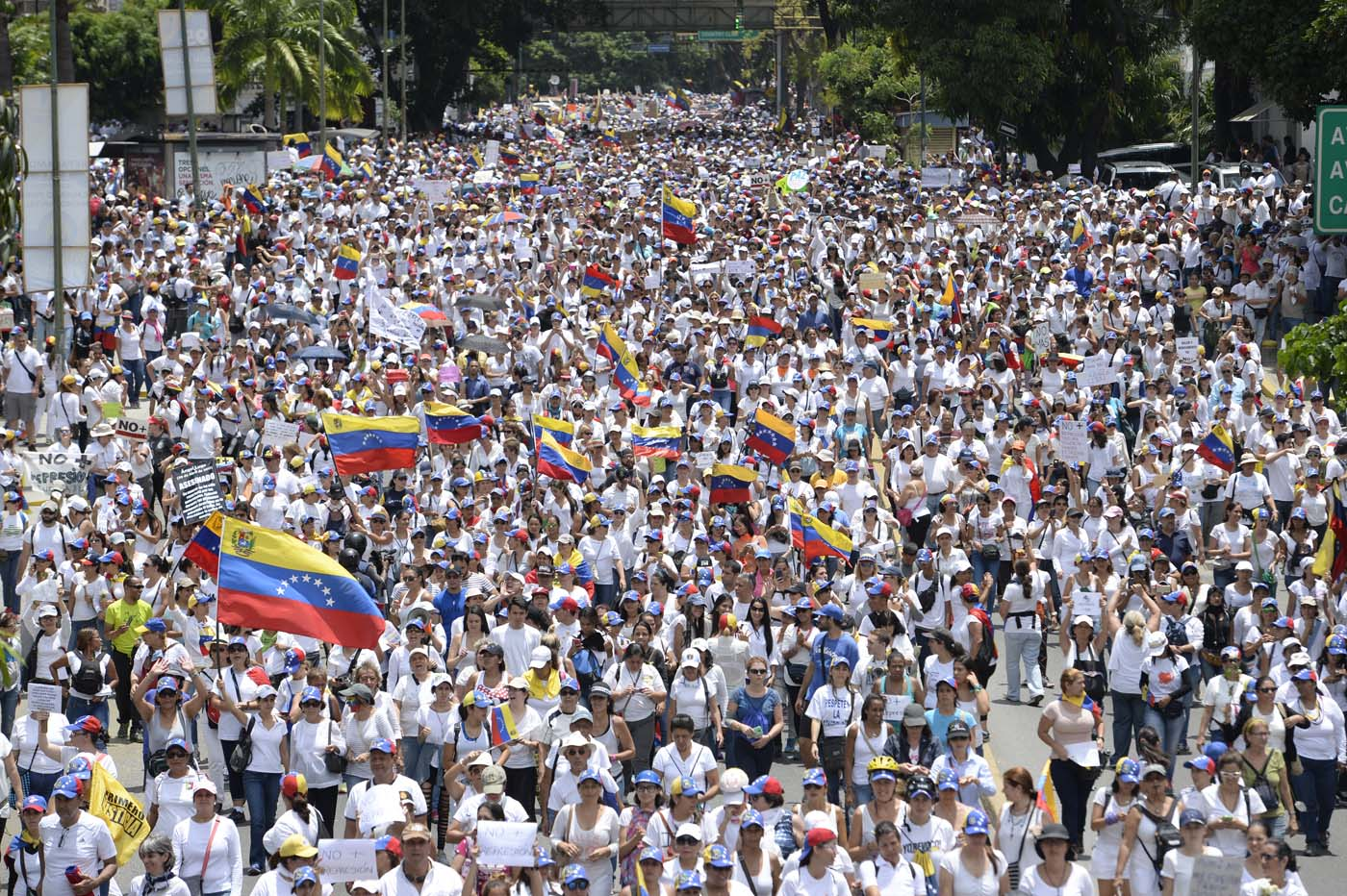 Venezuelan opposition activists take part in a women's march aimed to keep pressure on President Nicolas Maduro, whose authority is being increasingly challenged by protests and deadly unrest, in Caracas on May 6, 2017. The death toll since April, when the protests intensified after Maduro's administration and the courts stepped up efforts to undermine the opposition, is at least 36 according to prosecutors. / AFP PHOTO / FEDERICO PARRA