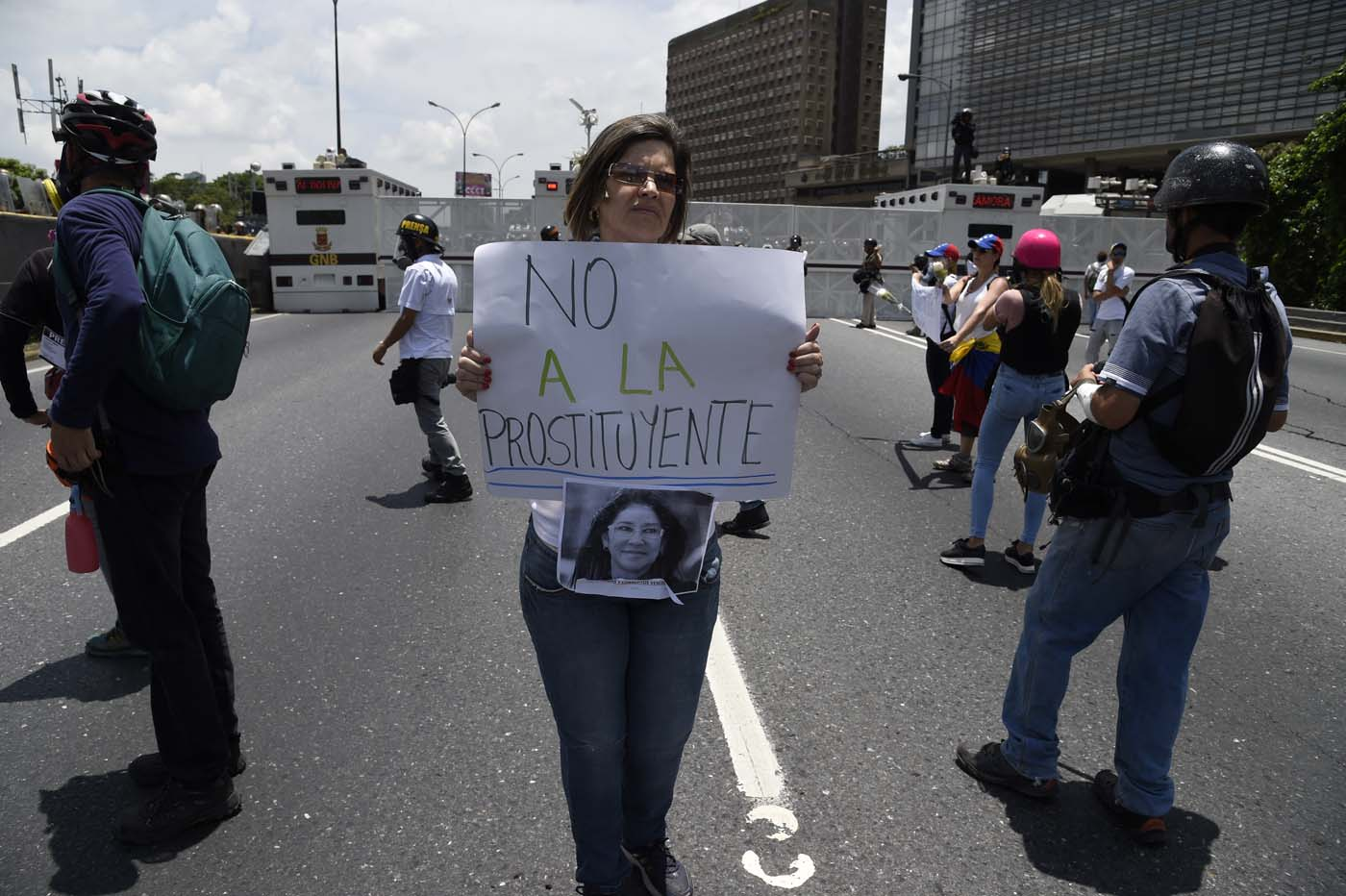 A Venezuelan opposition activist holds a sign against Venezuelan First Lady Cilia Flores during a women's march aimed to keep pressure on President Nicolas Maduro, whose authority is being increasingly challenged by protests and deadly unrest, in Caracas on May 6, 2017. The death toll since April, when the protests intensified after Maduro's administration and the courts stepped up efforts to undermine the opposition, is at least 36 according to prosecutors. / AFP PHOTO / JUAN BARRETO