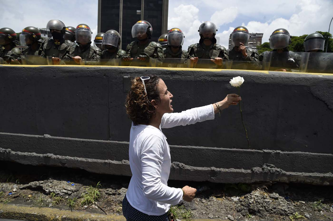 A Venezuelan opposition activist offers a flower to members of the Bolivarian National Guard standing guard during a women's march aimed to keep pressure on President Nicolas Maduro, whose authority is being increasingly challenged by protests and deadly unrest, in Caracas on May 6, 2017. The death toll since April, when the protests intensified after Maduro's administration and the courts stepped up efforts to undermine the opposition, is at least 36 according to prosecutors. / AFP PHOTO / JUAN BARRETO