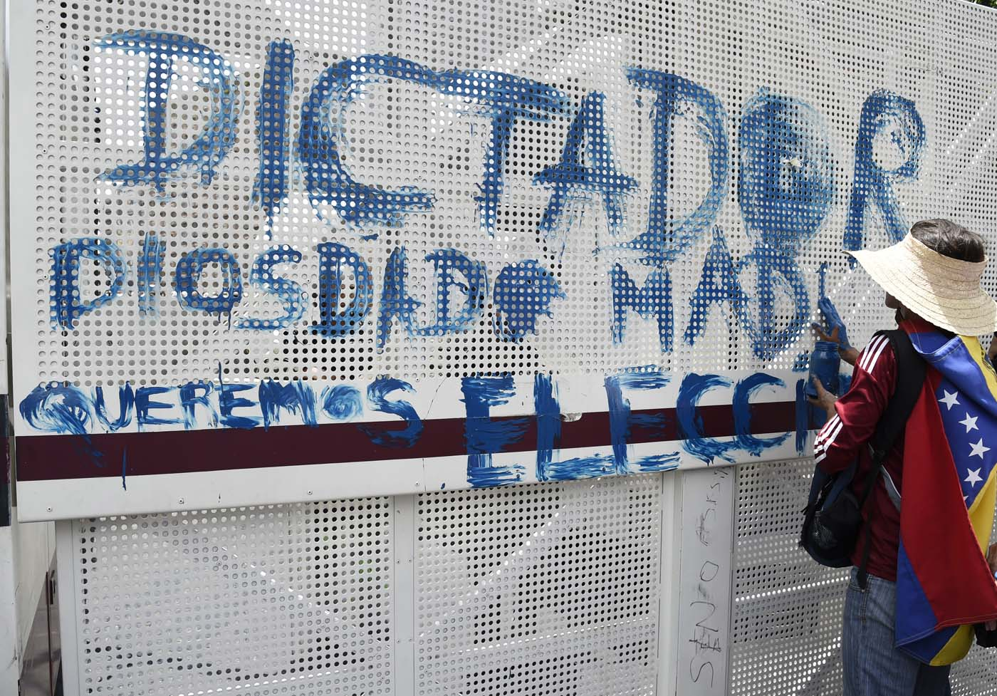 A Venezuelan opposition activist paints a graffiti on a fence during a women's march aimed to keep pressure on President Nicolas Maduro, whose authority is being increasingly challenged by protests and deadly unrest, in Caracas on May 6, 2017. The death toll since April, when the protests intensified after Maduro's administration and the courts stepped up efforts to undermine the opposition, is at least 36 according to prosecutors. / AFP PHOTO / JUAN BARRETO