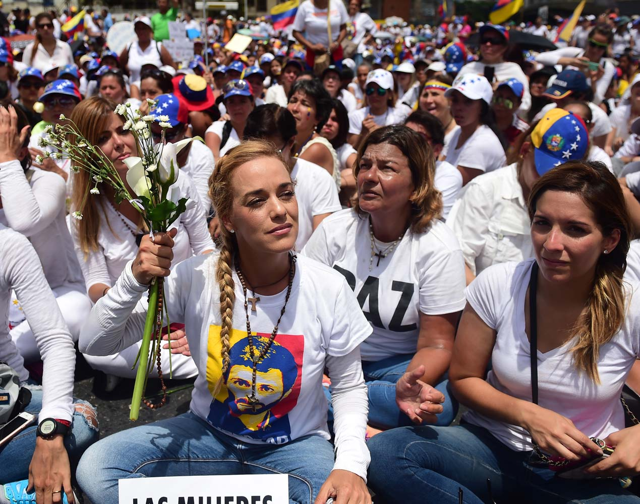 The wife of imprisoned opposition leader Leopoldo Lopez, Lilian Tintori (L), takes part in a women's march aimed to keep pressure on President Nicolas Maduro, whose authority is being increasingly challenged by protests and deadly unrest, in Caracas on May 6, 2017. The death toll since April, when the protests intensified after Maduro's administration and the courts stepped up efforts to undermine the opposition, is at least 36 according to prosecutors. / AFP PHOTO / RONALDO SCHEMIDT
