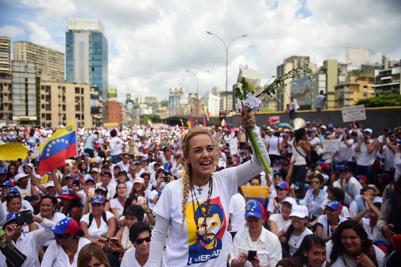The wife of imprisoned opposition leader Leopoldo Lopez, Lilian Tintori (C), takes part in a women's march aimed to keep pressure on President Nicolas Maduro, whose authority is being increasingly challenged by protests and deadly unrest, in Caracas on May 6, 2017. The death toll since April, when the protests intensified after Maduro's administration and the courts stepped up efforts to undermine the opposition, is at least 36 according to prosecutors. / AFP PHOTO / RONALDO SCHEMIDT