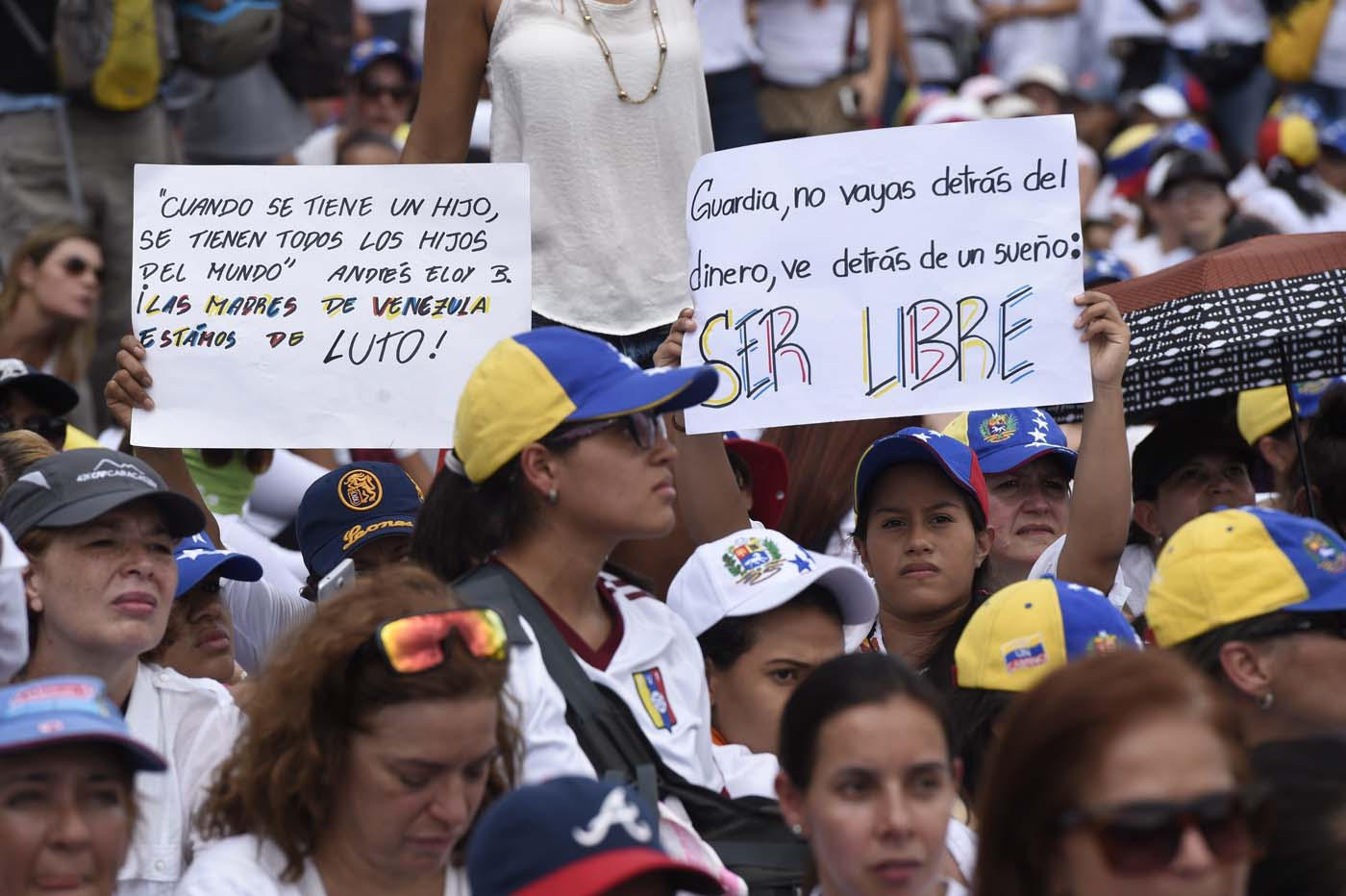 Venezuelan opposition activists take part in a women's march aimed to keep pressure on President Nicolas Maduro, whose authority is being increasingly challenged by protests and deadly unrest, in Caracas on May 6, 2017. The death toll since April, when the protests intensified after Maduro's administration and the courts stepped up efforts to undermine the opposition, is at least 36 according to prosecutors. / AFP PHOTO / JUAN BARRETO