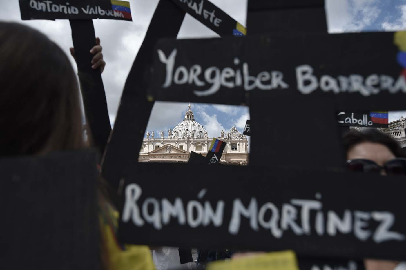 "Members of the Venezuelian community hold black crosses with names of victims of clashes with police during protests against Venezuela's President Nicolas Maduro, on May 7, 2017  at St Peter's square before the Regina Coeli prayer of Pope Francis in Vatican. Pope Francis last week made a heartfelt appeal for ""negotiated solutions"" to end the violence in crisis-torn Venezuela for the sake of an ""exhausted population"".  The death toll since April -- when the protests intensified after Maduro's administration and the courts stepped up efforts to undermine the opposition -- is at least 36, according to prosecutors, with hundreds more injured. / AFP PHOTO / TIZIANA FABI"