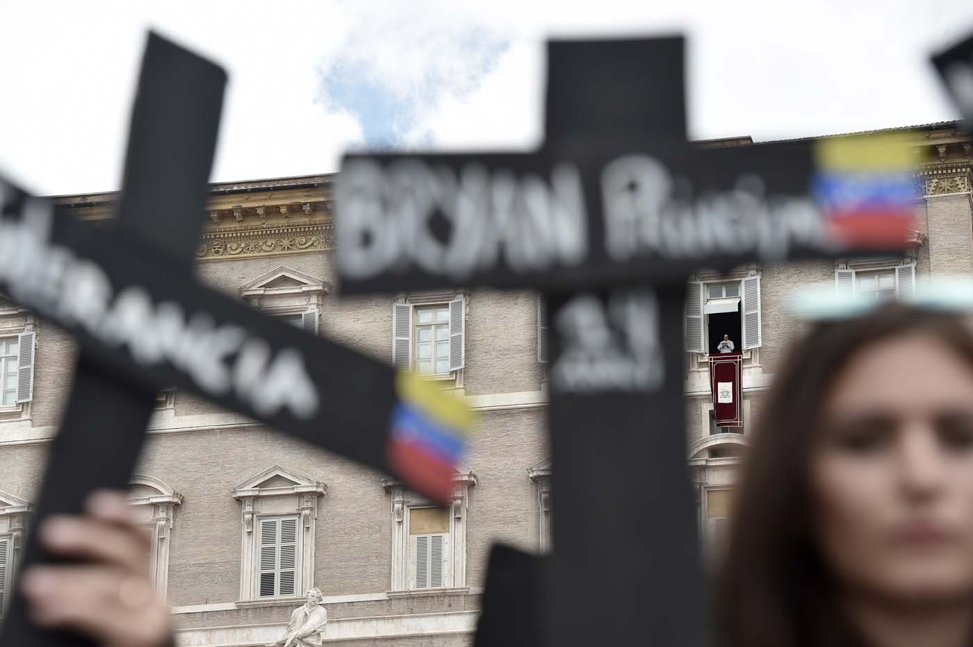 "Members of the Venezuelian community hold black crosses with names of victims of clashes during protests against Venezuela's President Nicolas Maduro, on May 7, 2017 at St Peter's square as Pope Francis stands at the window of the apostolic palace during the Regina Coeli prayer in Vatican. Pope Francis last week made a heartfelt appeal for ""negotiated solutions"" to end the violence in crisis-torn Venezuela for the sake of an ""exhausted population"". The death toll since April -- when the protests intensified after Maduro's administration and the courts stepped up efforts to undermine the opposition -- is at least 36, according to prosecutors, with hundreds more injured. / AFP PHOTO / TIZIANA FABI"