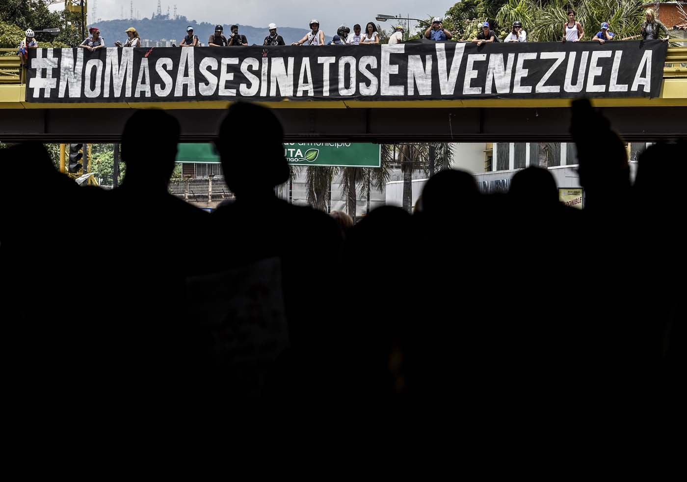 View of a banner reading #NoMoreKillingsInVenezuela during a demonstration in rejection of the recent deaths of young people by security forces -within opposition protests- in Caracas on May 7, 2017. The last death in Venezuela's unrest, of a 22-year-old man, occurred during looting in Valencia, one of Venezuelan cities hardest hit by a worsening economic crisis. Demonstrators blame Maduro for the country's plight and the shortages of food and medicine, and demand elections to remove the leftist president.  / AFP PHOTO / JUAN BARRETO