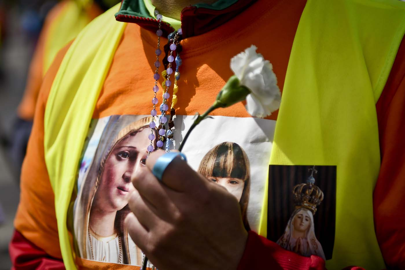 A pilgrim sporting a t-shirt with the image of Our Lady of Fatima, holds a carnation at Fatima, central Portugal, on May 11, 2017.  Two of the three child shepherds who reported apparitions of the Virgin Mary in Fatima, Portugal, one century ago, will be declared saints on May 13, 2017 by Pope Francis. The canonisation of Jacinta and Francisco Marto will take place during the Argentinian pontiff's visit to a Catholic shrine visited by millions of pilgrims every year. / AFP PHOTO / PATRICIA DE MELO MOREIRA